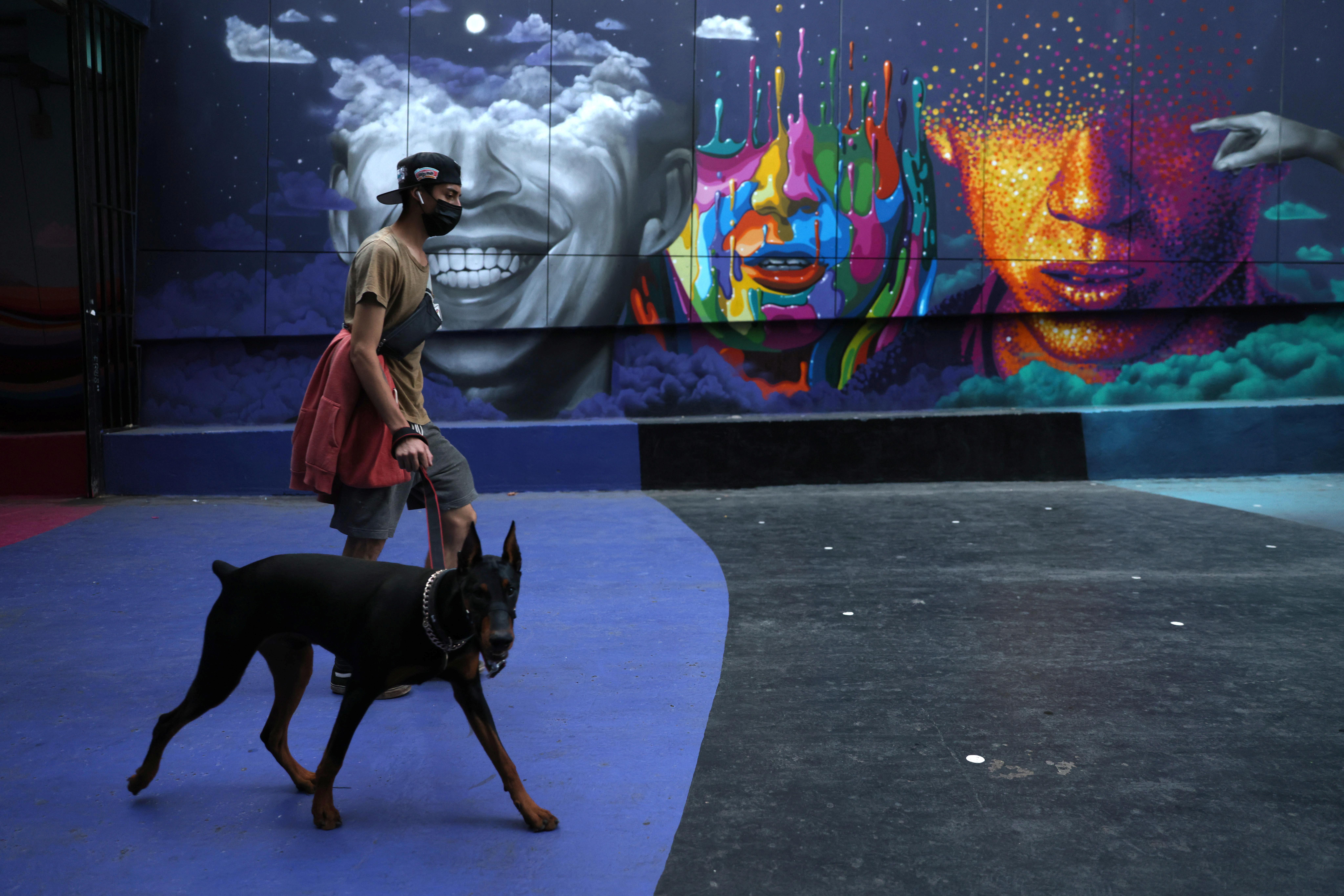 A man walks a dog as lockdown restrictions increase during the coronavirus disease (COVID-19) outbreak, in Santiago, Chile, March 31, 2021. REUTERS/Ivan Alvarado