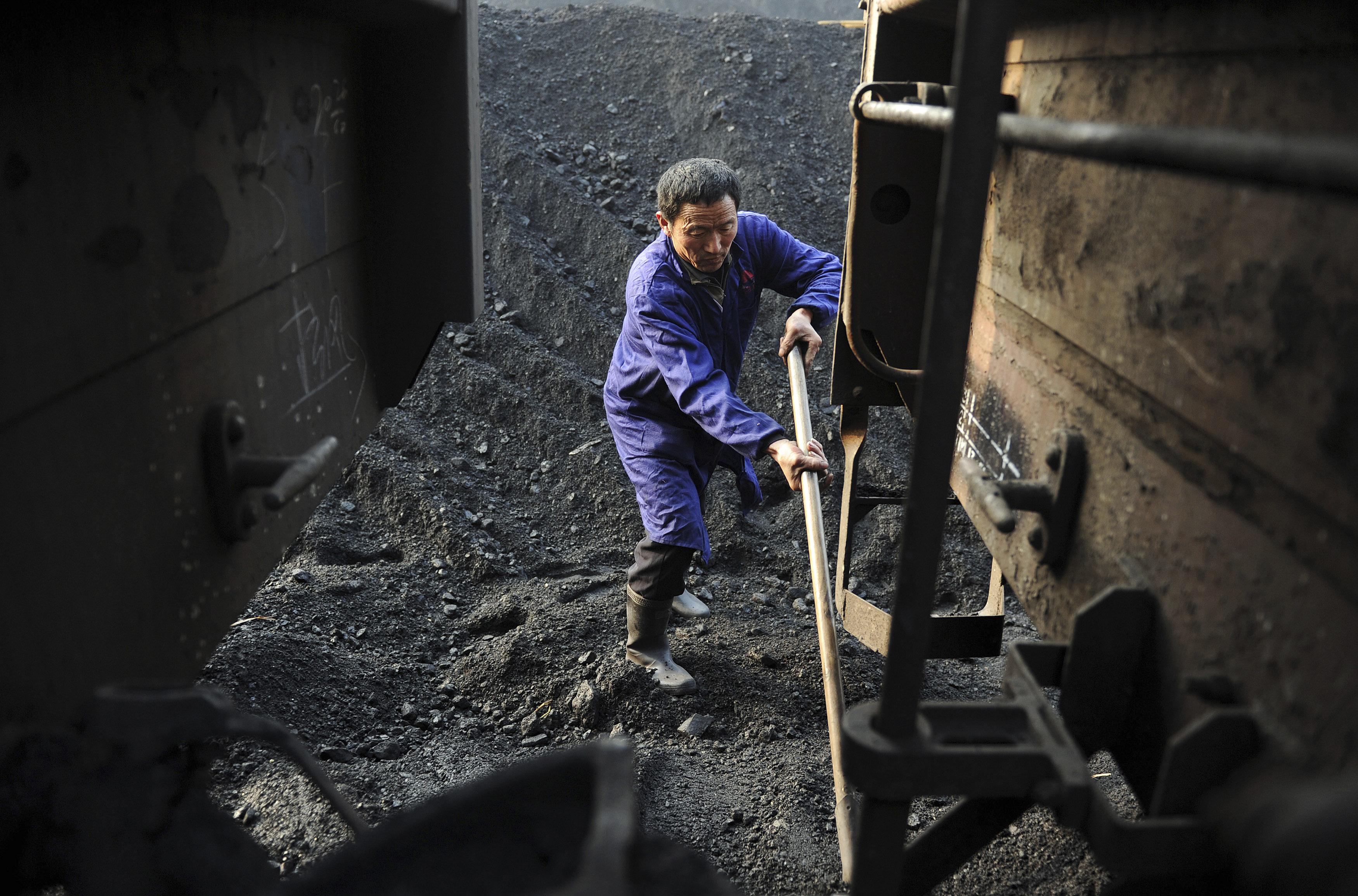 A worker shovels coal onto a freight train at a freight yard in Hefei, Anhui province, January 13, 2013. REUTERS/Stringer