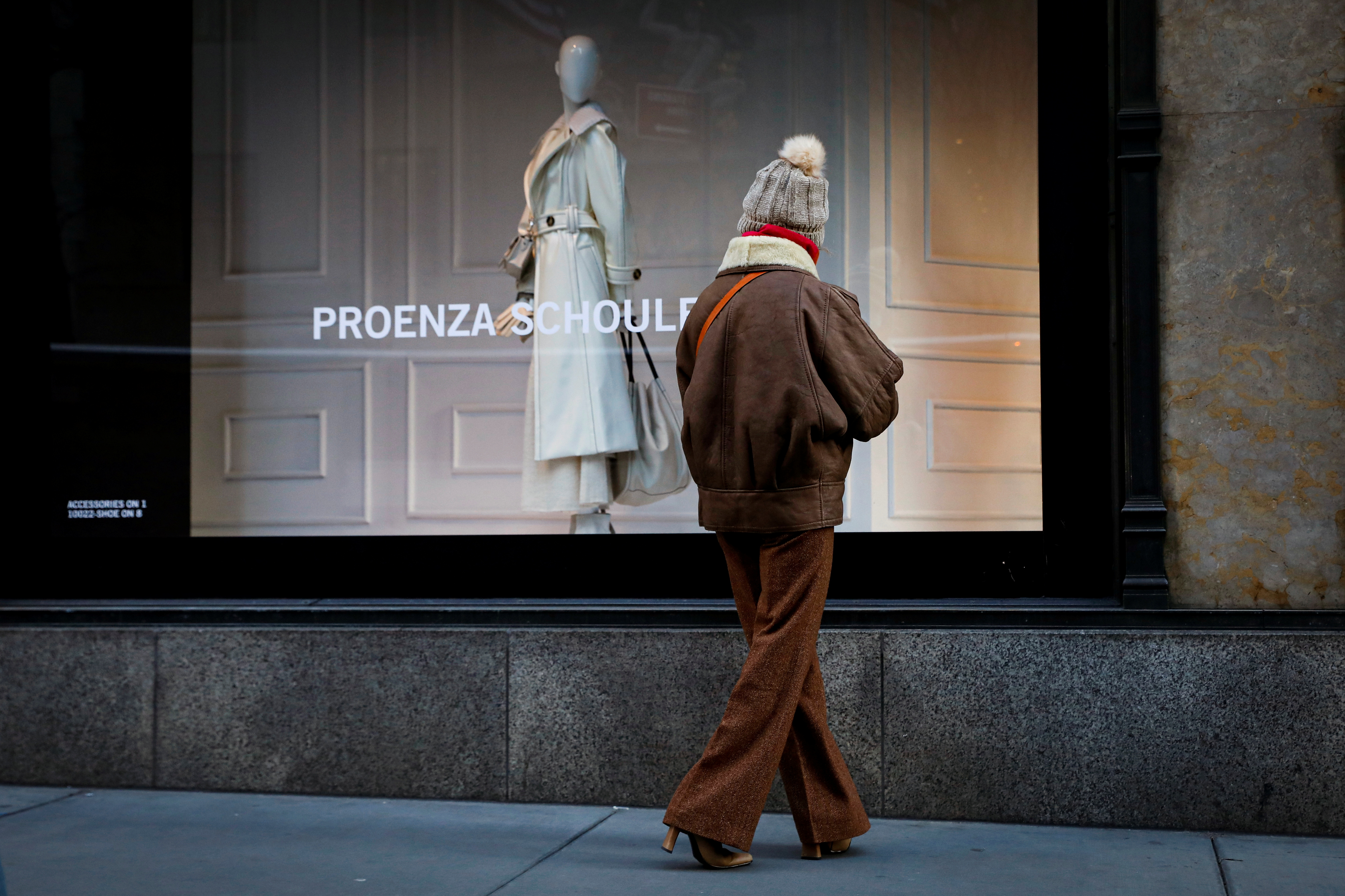 A woman looks at a window featuring fashion by Proenza Schouler at Saks 5th Ave, during the coronavirus disease (COVID-19) pandemic, in New York, U.S., February 17, 2021.  REUTERS/Brendan McDermid