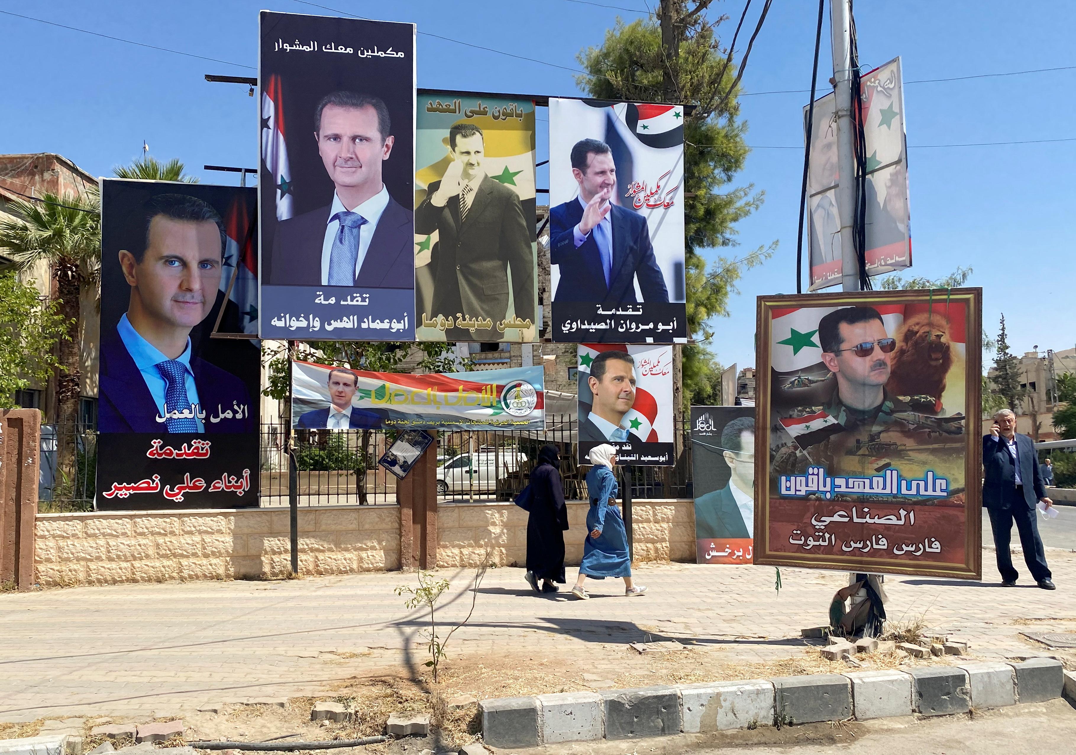 Poster di Bashar al-Assad tappezzano le strade durante le elezioni in Siria. Douma, 26 maggio 2021. Credits to: REUTERS/Firas Makdesi.