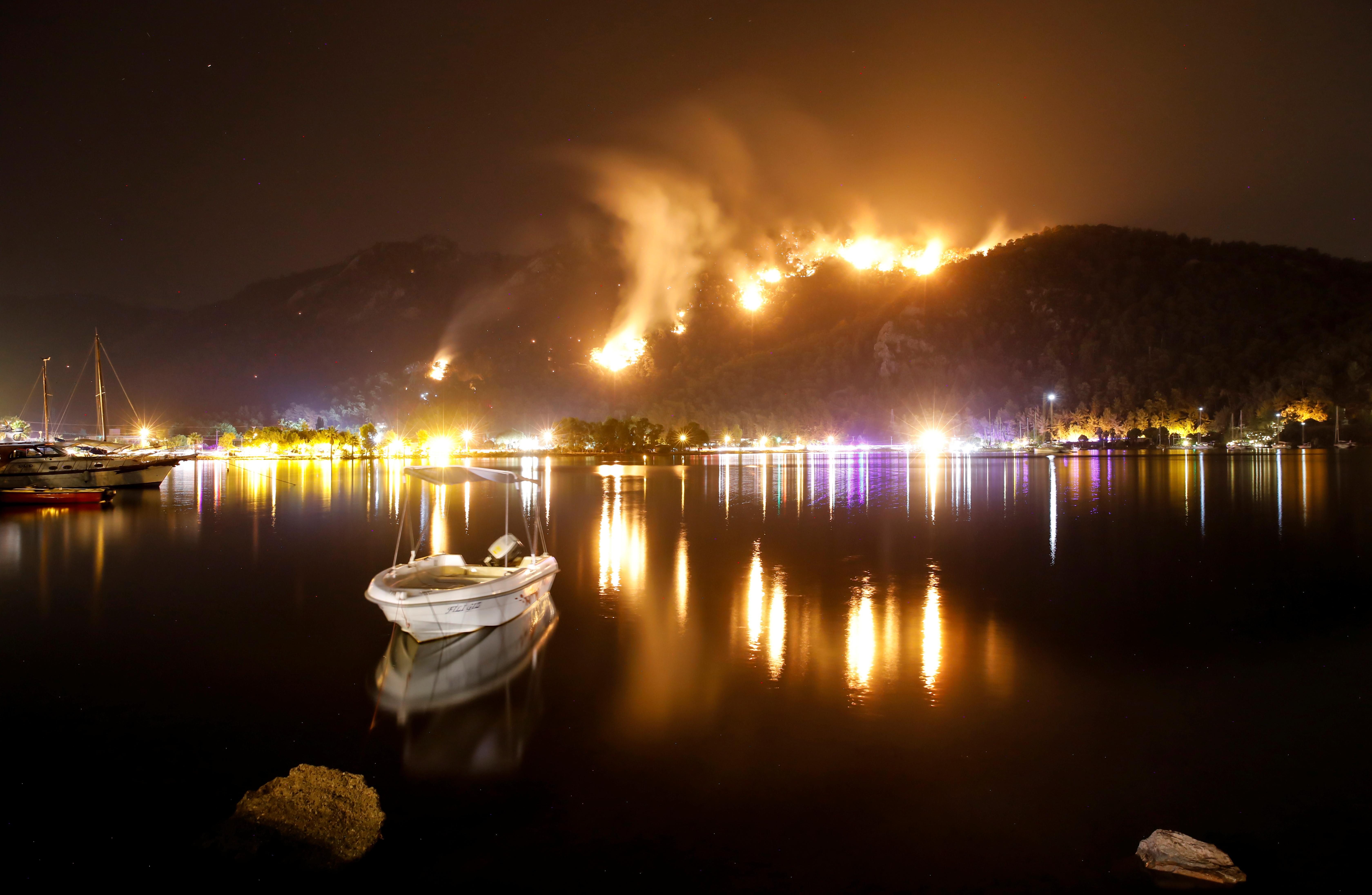 Flames and smoke rises from mountains in Orhaniye village near Marmaris, Turkey, August 4, 2021. REUTERS/Umit Bektas