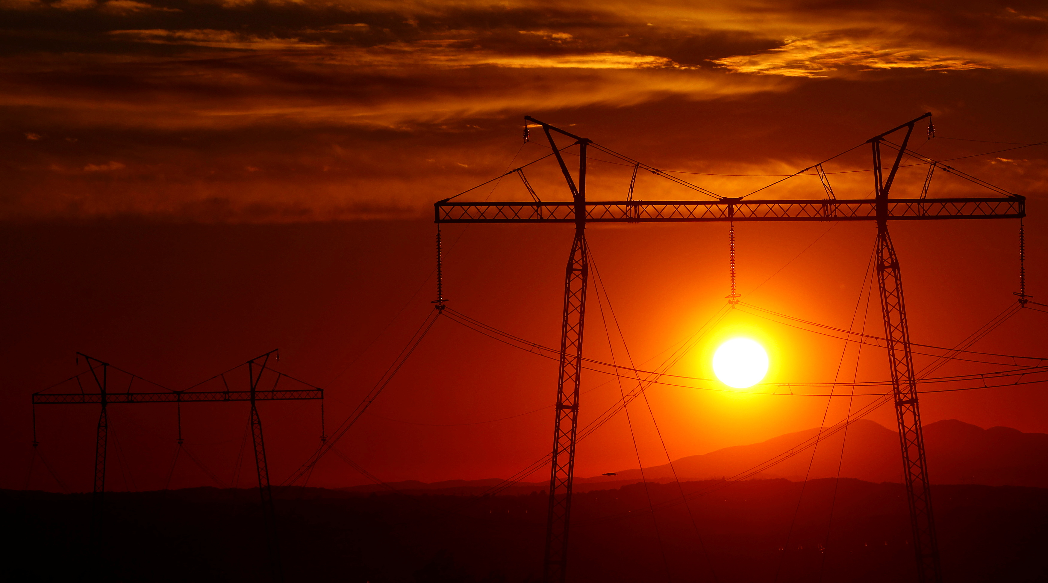 The sun sets behind electric power transmission lines near the town of Sachkhere, some 200 km (124 miles) north-west of Tbilisi, September 13, 2013. REUTERS/David Mdzinarishvili/File Photo