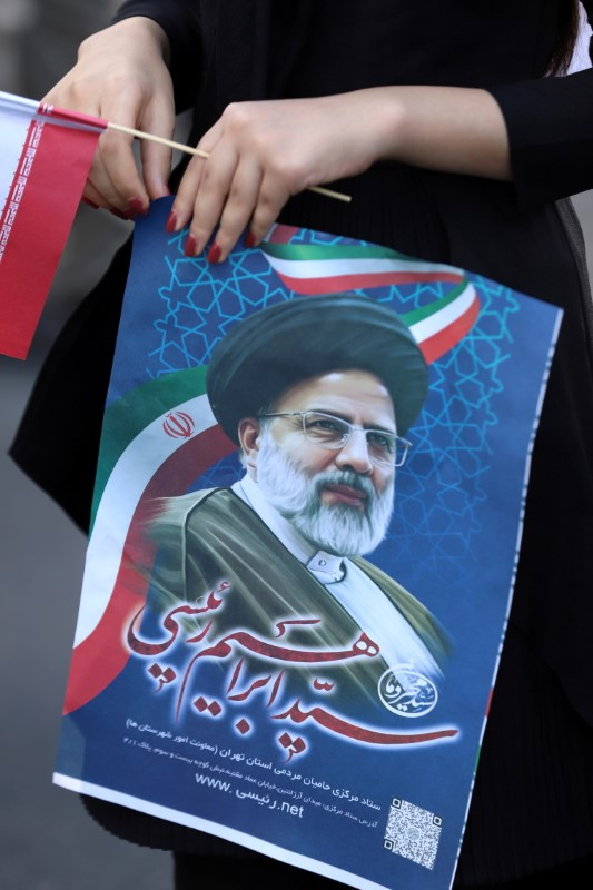 A supporter of presidential candidate Ebrahim Raisi holds a poster of him during an election rally in Tehran, Iran June 11, 2021. Picture taken June 11, 2021. Majid Asgaripour/WANA (West Asia News Agency) via REUTERS