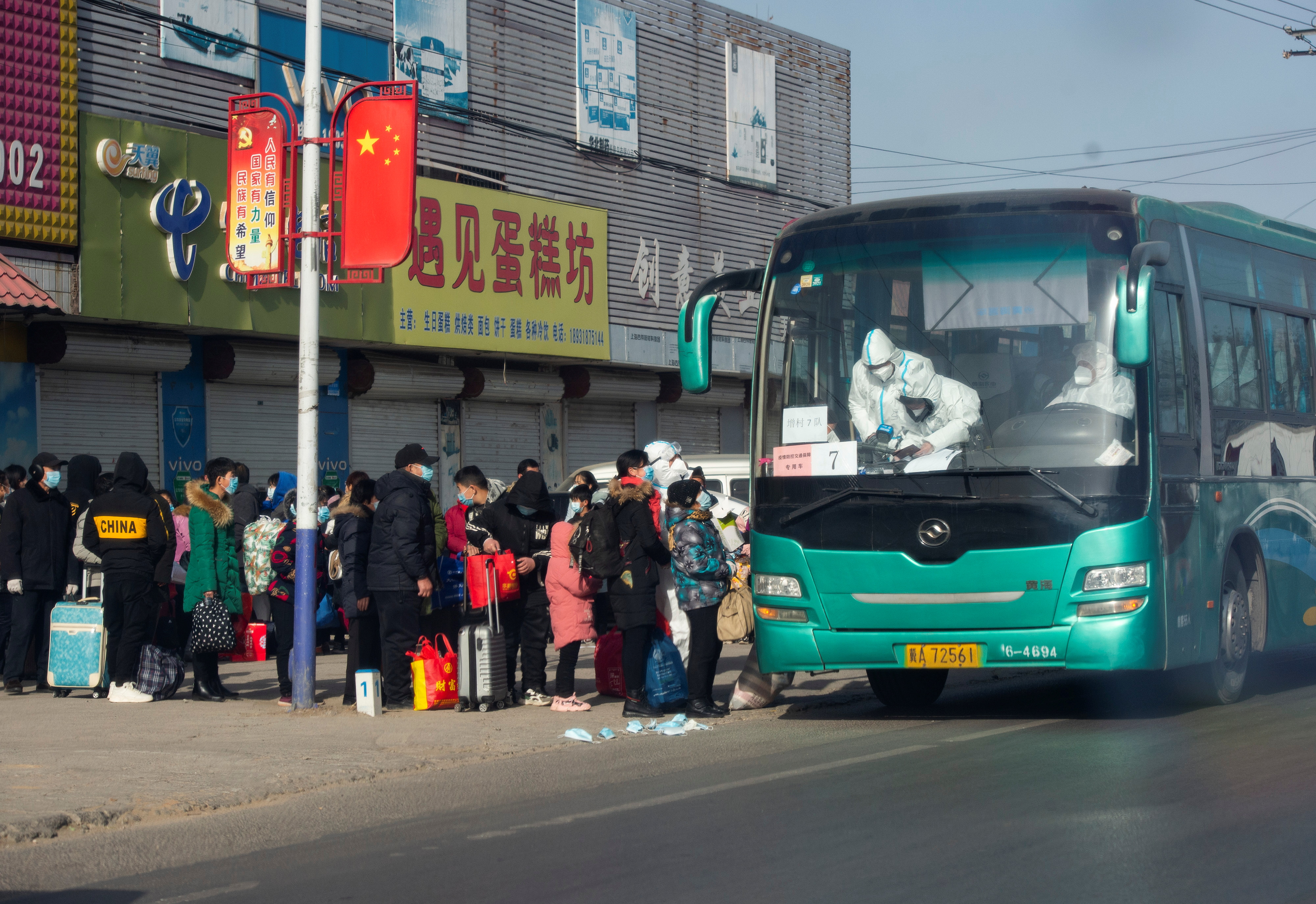 People who are required to undergo centralized quarantine line up to board a bus at a village in Gaocheng district, following a recent outbreak of the coronavirus disease (COVID-19) in Shijiazhuang, Hebei province, China January 11, 2021. cnsphoto via REUTERS   ATTENTION EDITORS - THIS IMAGE WAS PROVIDED BY A THIRD PARTY. CHINA OUT.