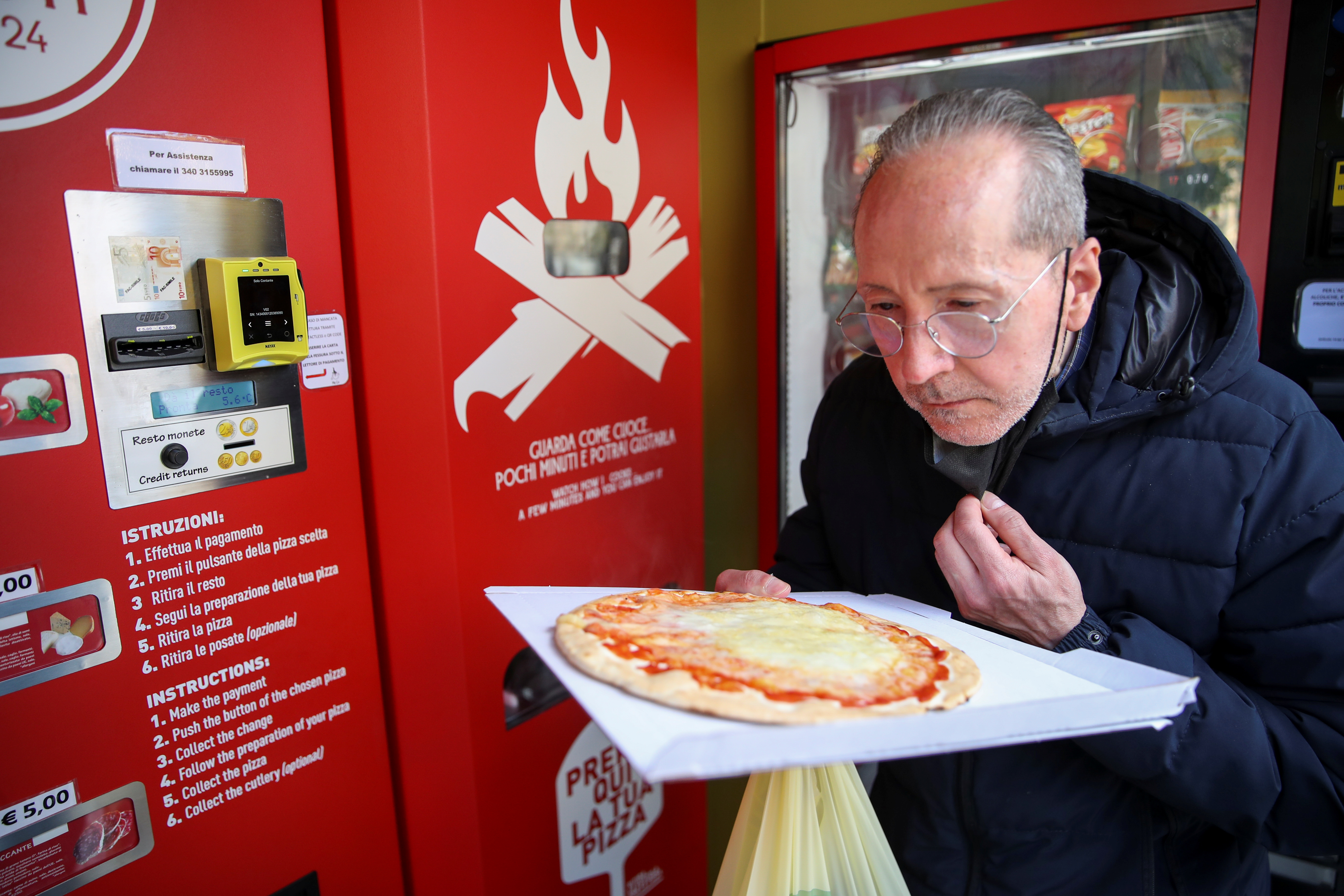 Claudio Zampiga sniffs his pizza at the first automatic pizza vending machine, which is capable of kneading, seasoning and cooking the pizza in three minutes, in Rome, Italy, May 6, 2021. REUTERS/Yara Nardi