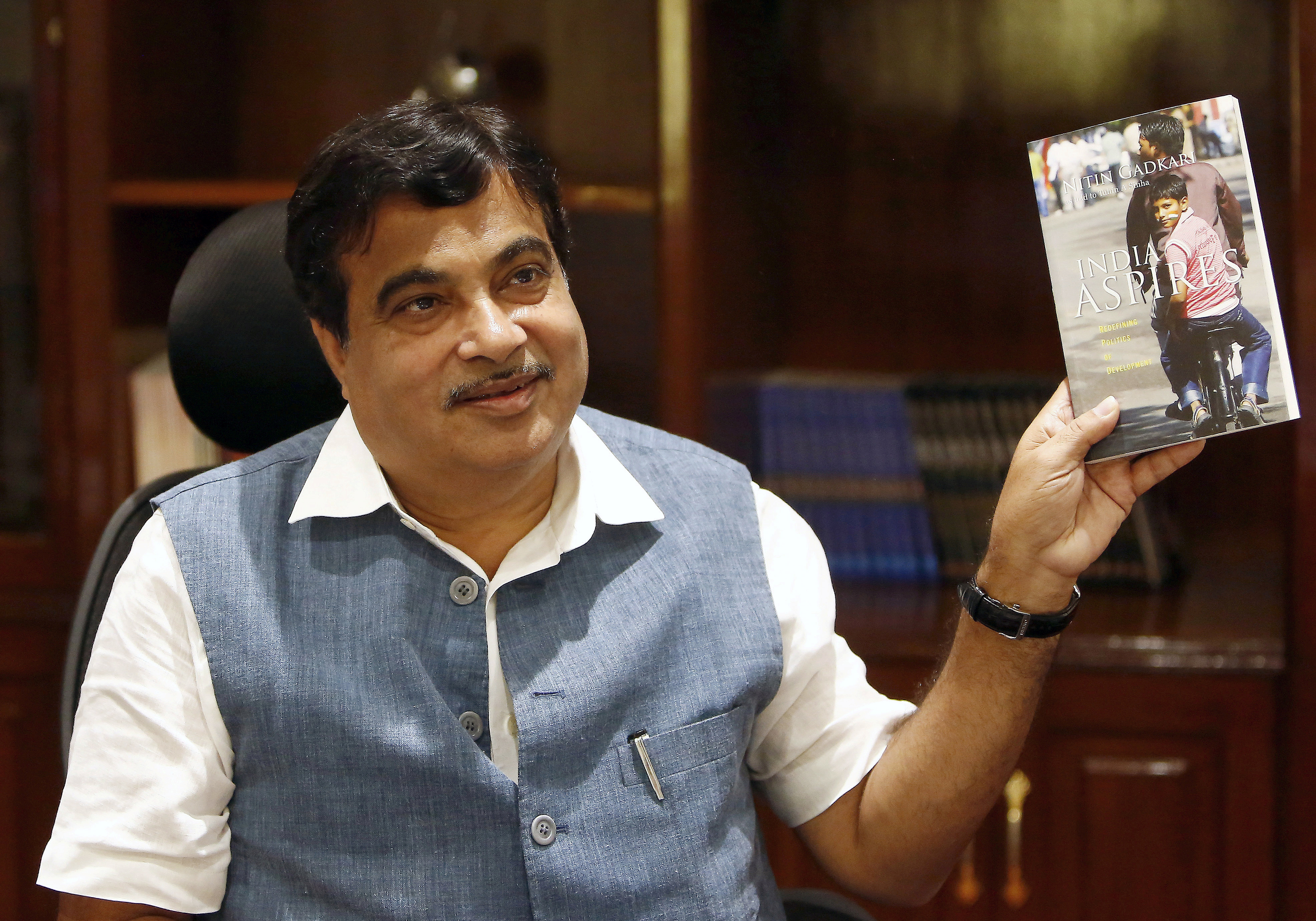 India's Transport and Shipping Minister Nitin Gadkari displays a book written by him at his office in New Delhi, India August 26, 2015. REUTERS/Anindito Mukherjee/File Photo