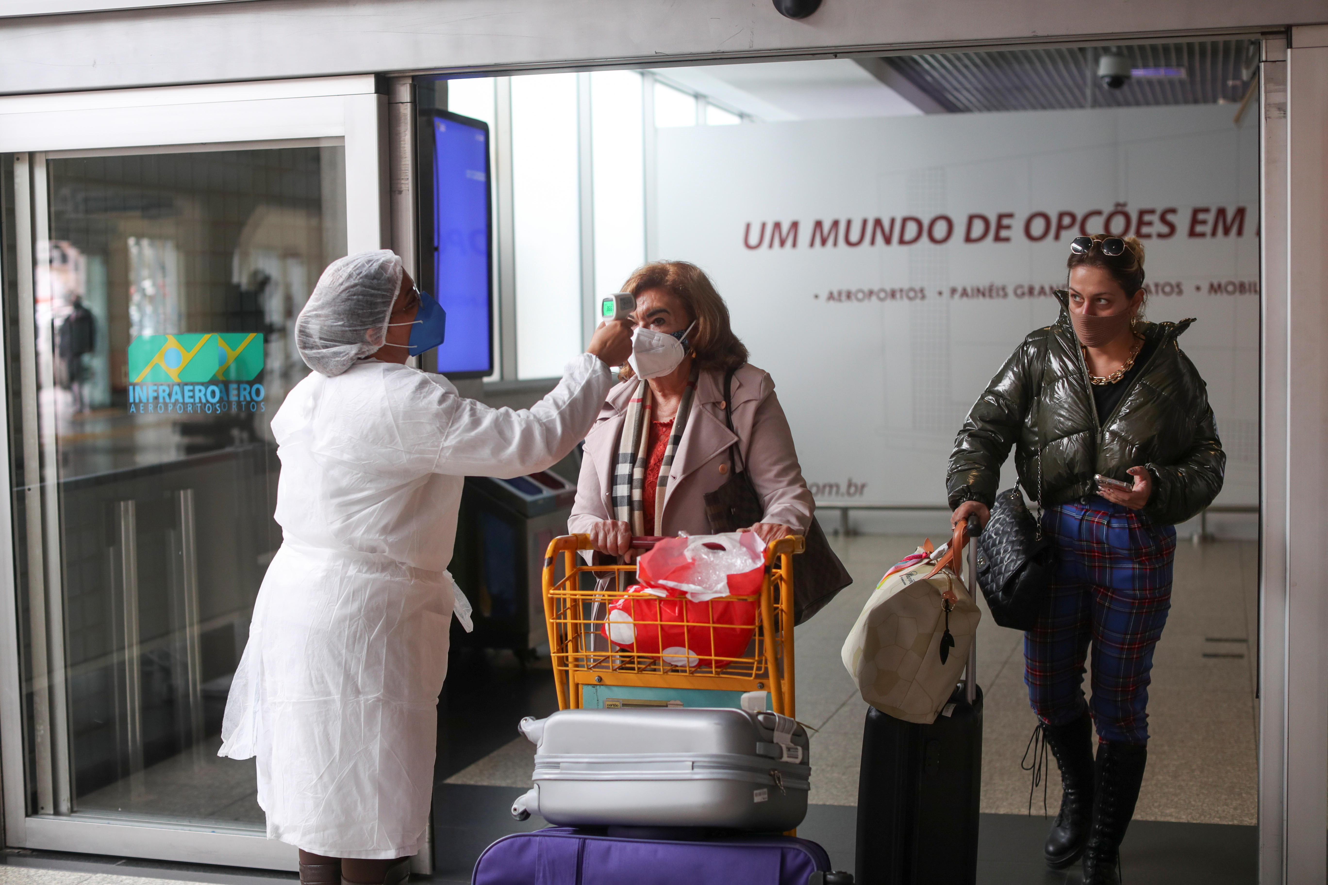 A health worker measures the temperature of a traveller in a sanitary barrier as she arrives at Congonhas airport in Sao Paulo, Brazil May 31, 2021. REUTERS/Amanda Perobelli