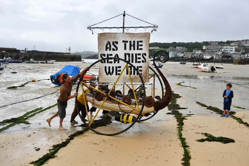 Climate change activists push a boat with a banner during a protest in St. Ives, on the sidelines of G7 summit in Cornwall, Britain, June 11, 2021. REUTERS/Dylan Martinez