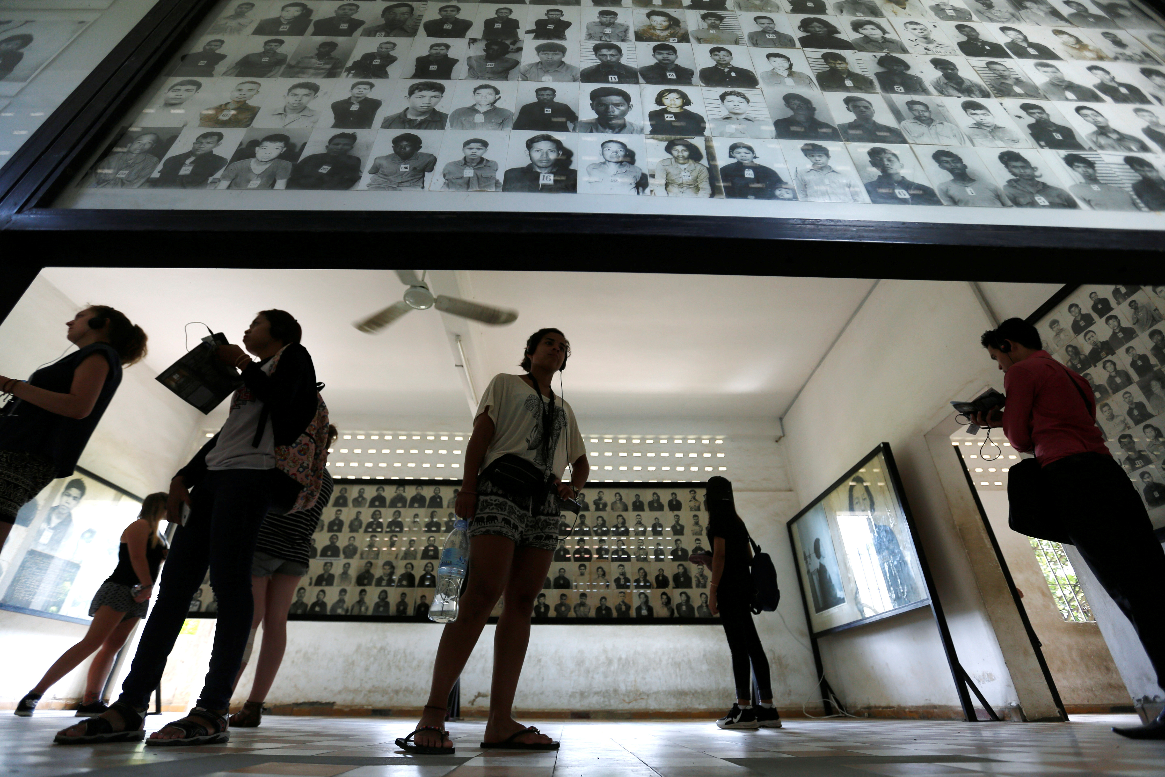 A visitor looks at pictures of victims of the Khmer Rouge regime at Tuol Sleng Genocide Museum in Phnom Penh, Cambodia June 1, 2016. REUTERS/Samrang Pring