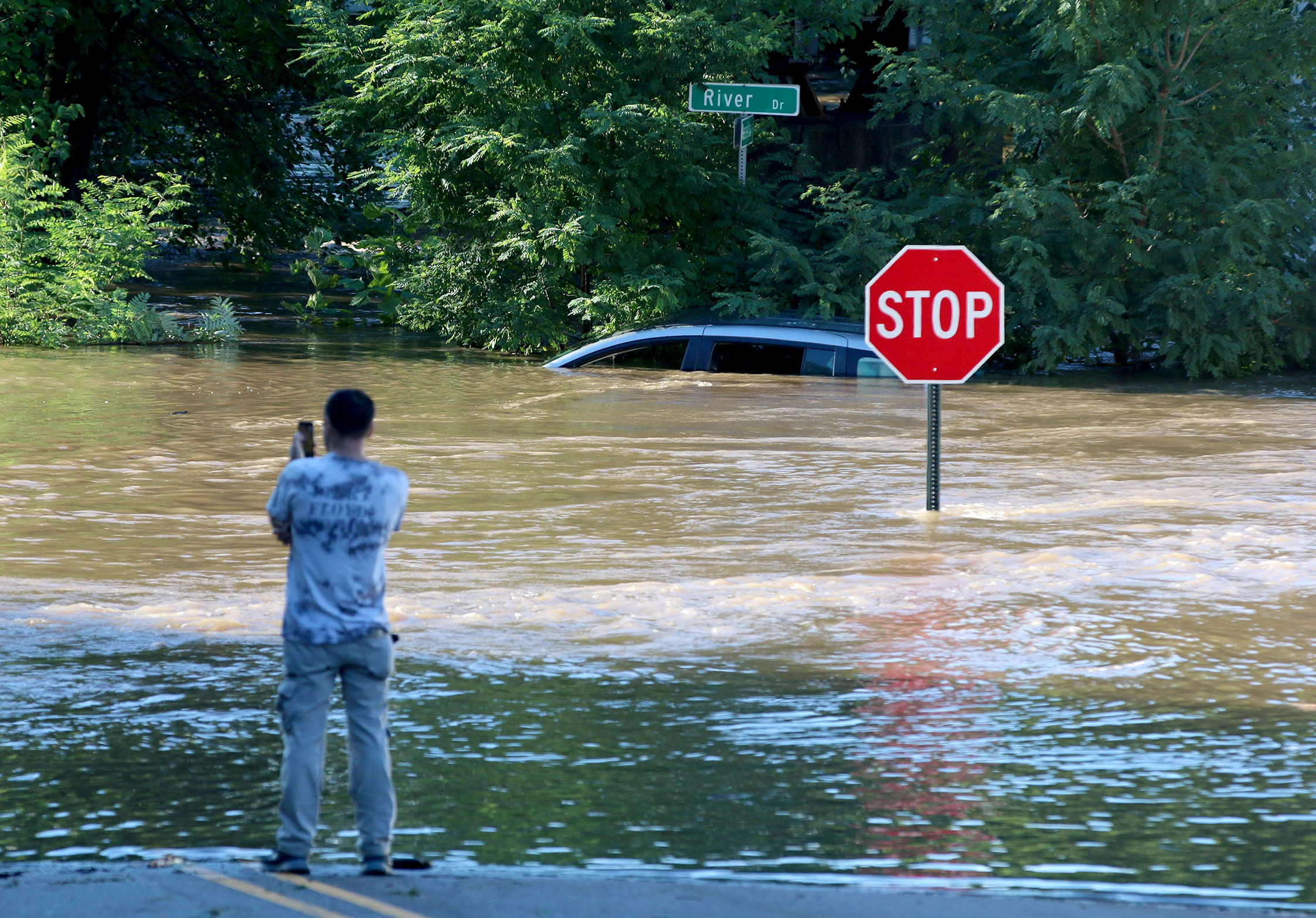 A man takes photos of a submerged car as the remnants of Hurricane Ida brought torrential rains and flooding to the area in Passaic, New Jersey, September 2. Thomas P. Costello/USA TODAY Network via REUTERS