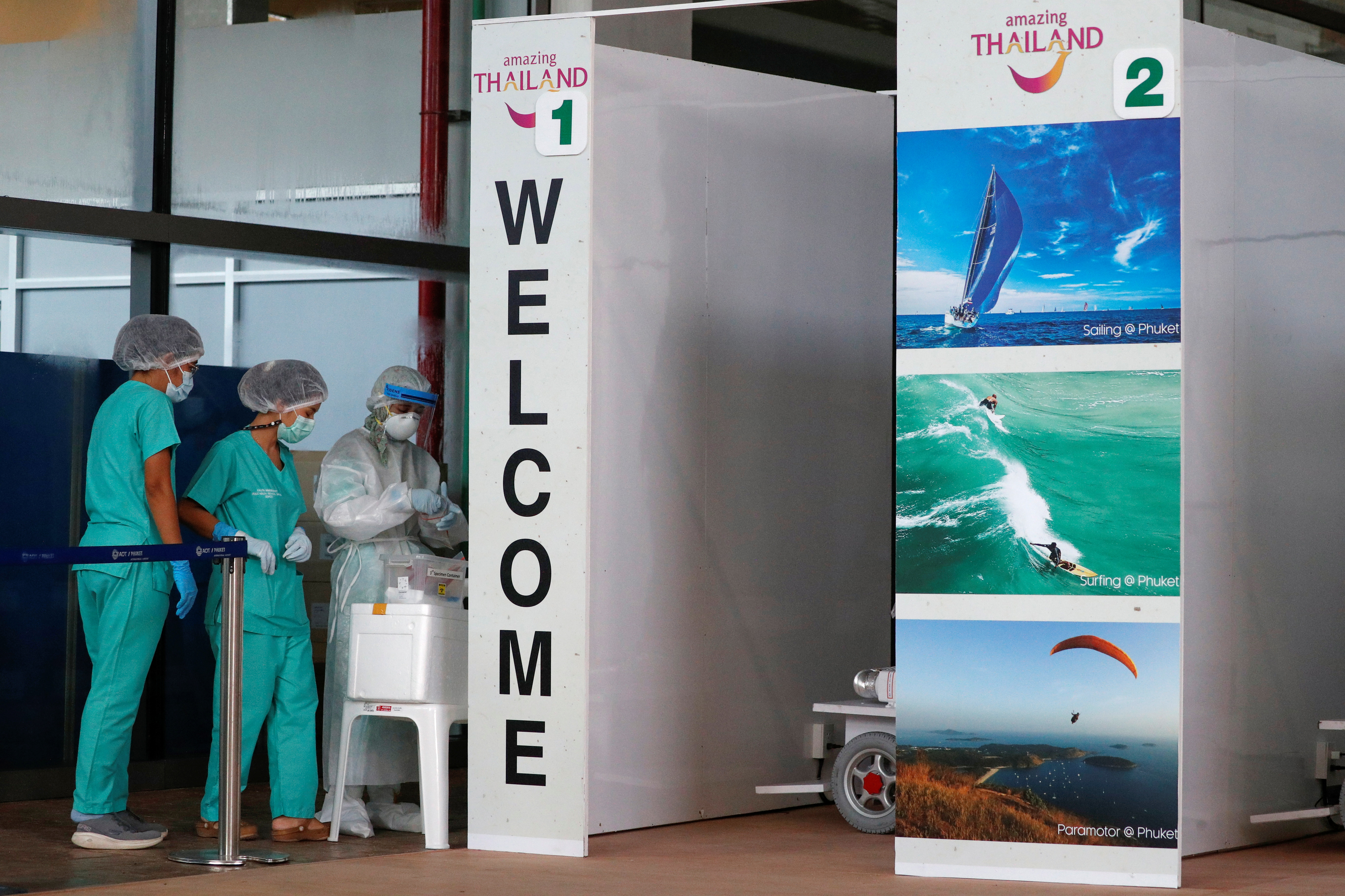 Health workers stand at the COVID-19 swab test area at the airport as Phuket reopens to overseas tourists, allowing foreigners fully vaccinated against the coronavirus disease (COVID-19) to visit the resort island without quarantine, in Phuket, Thailand July 1, 2021. REUTERS/Jorge Silva