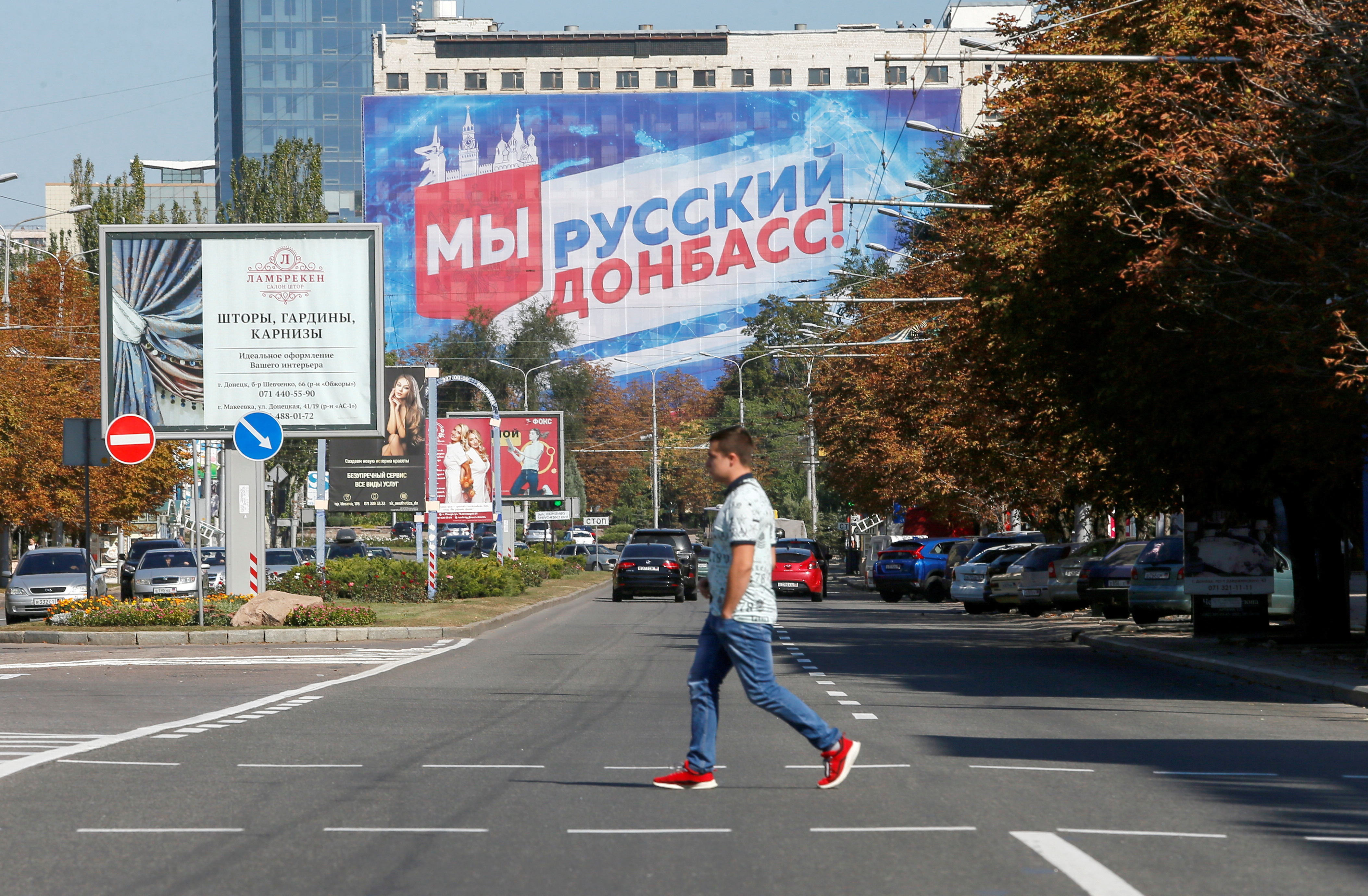 A pedestrian crosses a street near a building with a banner displaying the slogan