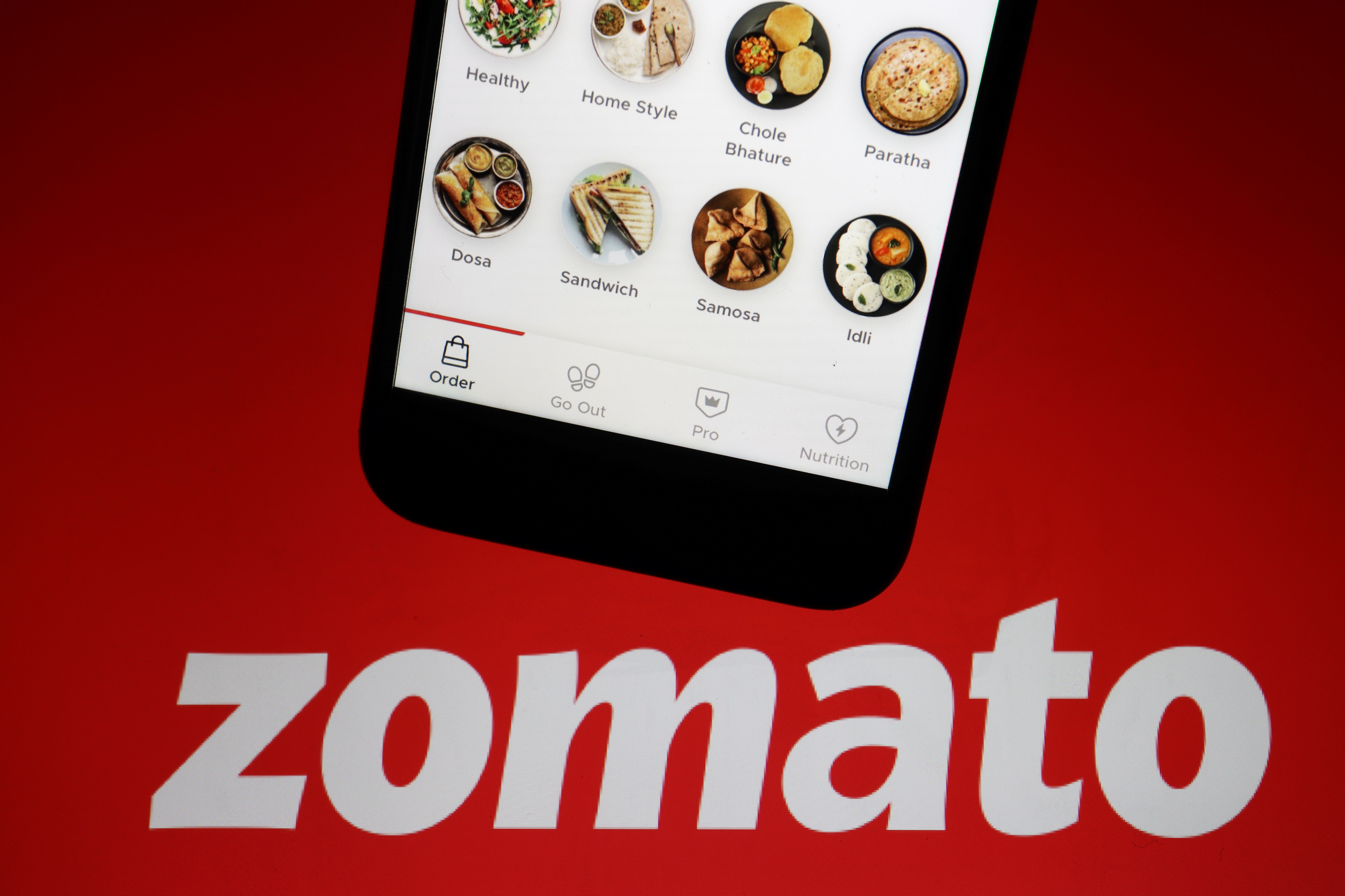 The app of Indian food delivery company Zomato is seen on a mobile phone above its logo displayed in this illustration picture taken July 14, 2021. REUTERS/Florence Lo/Illustration/File photo
