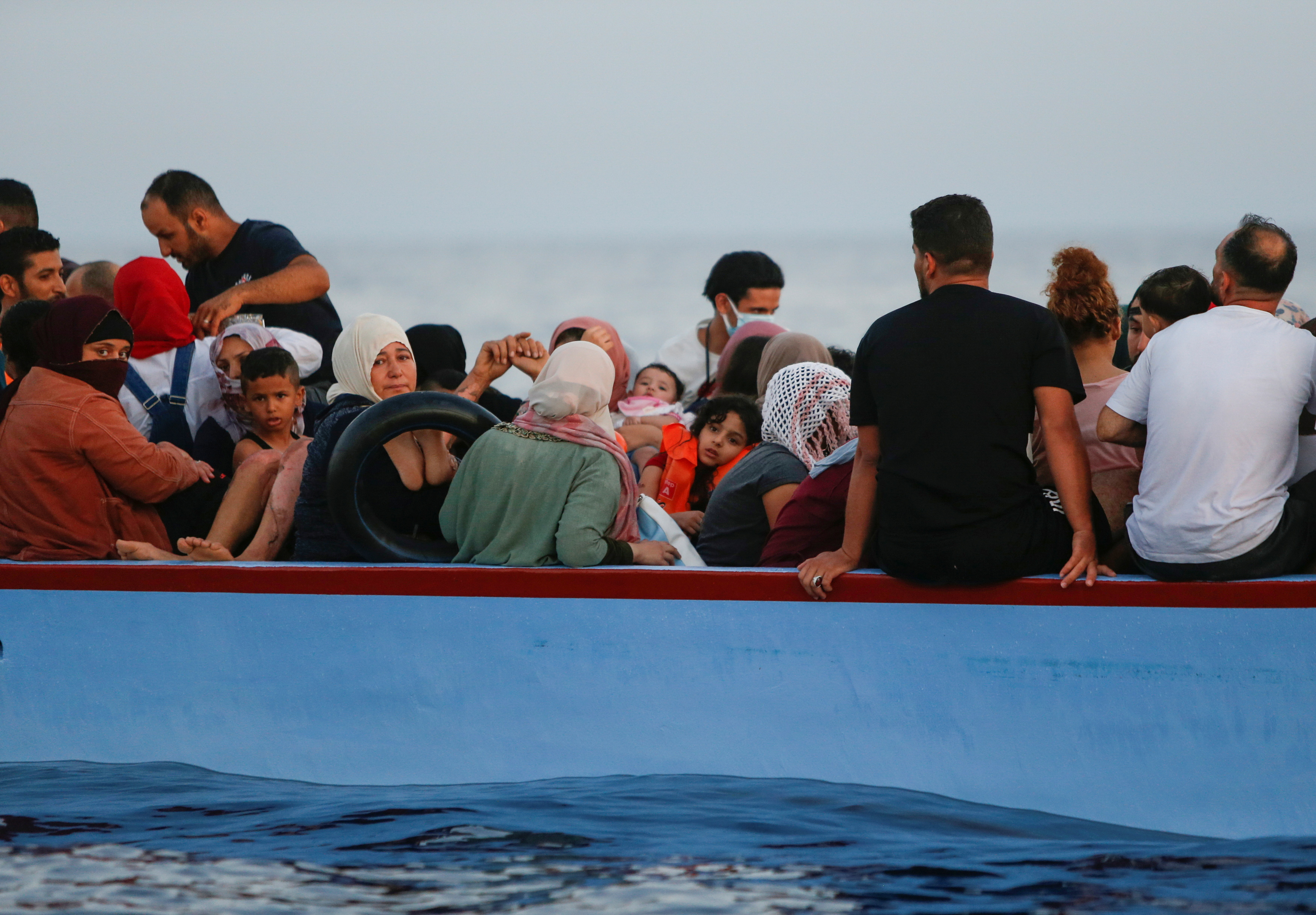 Migrants wait in a wooden boat to be rescued by the German NGO migrant rescue ship Sea-Watch 3 in international waters off the coast of Libya, in the western Mediterranean Sea, July 30, 2021.  REUTERS/Darrin Zammit Lupi