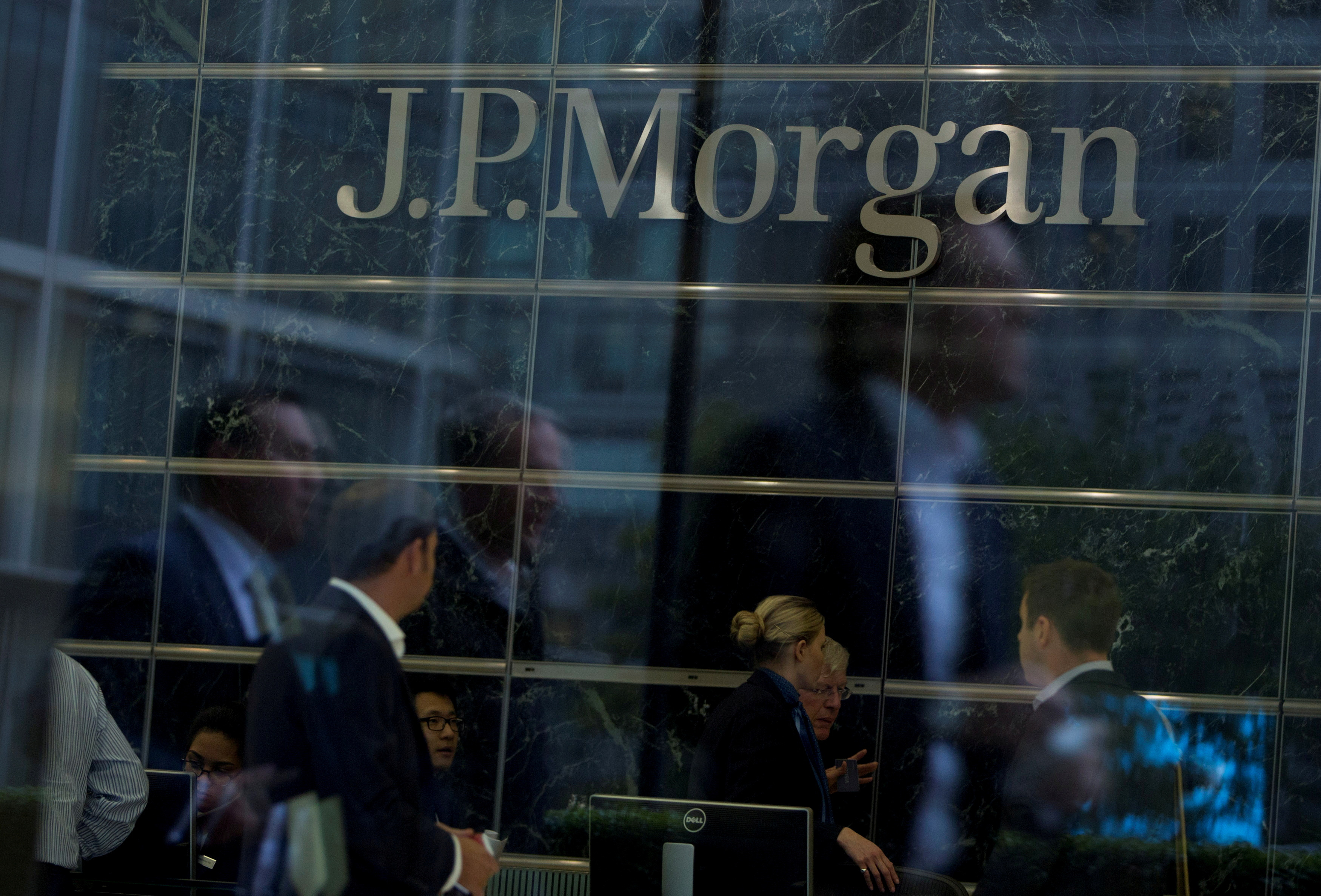 Workers are reflected in the windows of the Canary Wharf offices of JP Morgan in London September 19, 2013. REUTERS/Neil Hall/File Photo