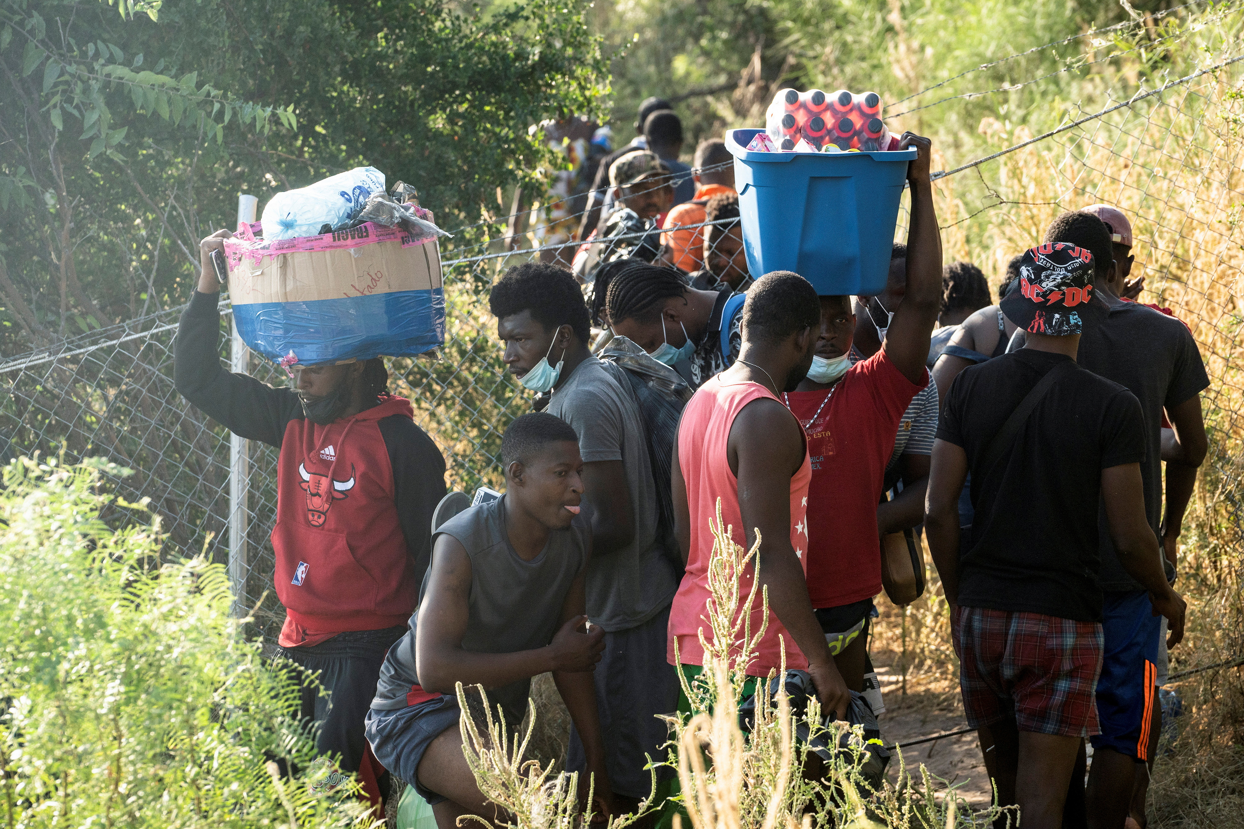 Migrants seeking asylum in the U.S. carry food and supplies as they wait to be processed, in Ciudad Acuna, Mexico, September 16, 2021. According to officials, some migrants cross back and forth into Mexico to buy food and supplies. REUTERS/Go Nakamura