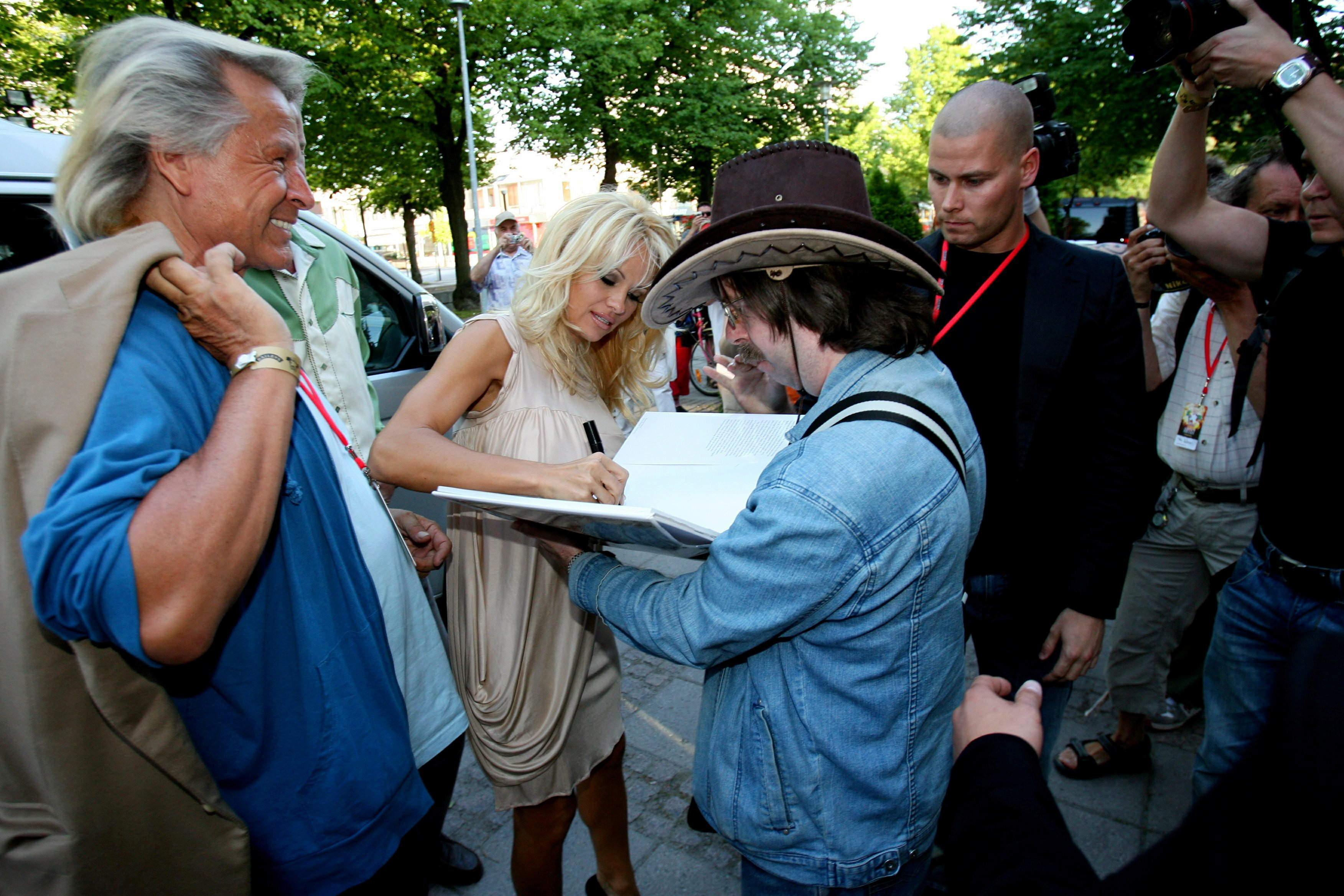 Actress Pamela Anderson signs an autograph for fan Juha Nurmi while Finnish-born fashion designer Peter Nygard looks on at the Raumanmeri midsummer festival in Rauma, Finland, June 22, 2007. Picture taken June 22, 2007.  Lehtikuva/Roni Rekomaa via REUTERS      ATTENTION EDITORS - THIS IMAGE WAS PROVIDED BY A THIRD PARTY. NO THIRD PARTY SALES. NOT FOR USE BY REUTERS THIRD PARTY DISTRIBUTORS. FINLAND OUT. NO COMMERCIAL OR EDITORIAL SALES IN FINLAND.