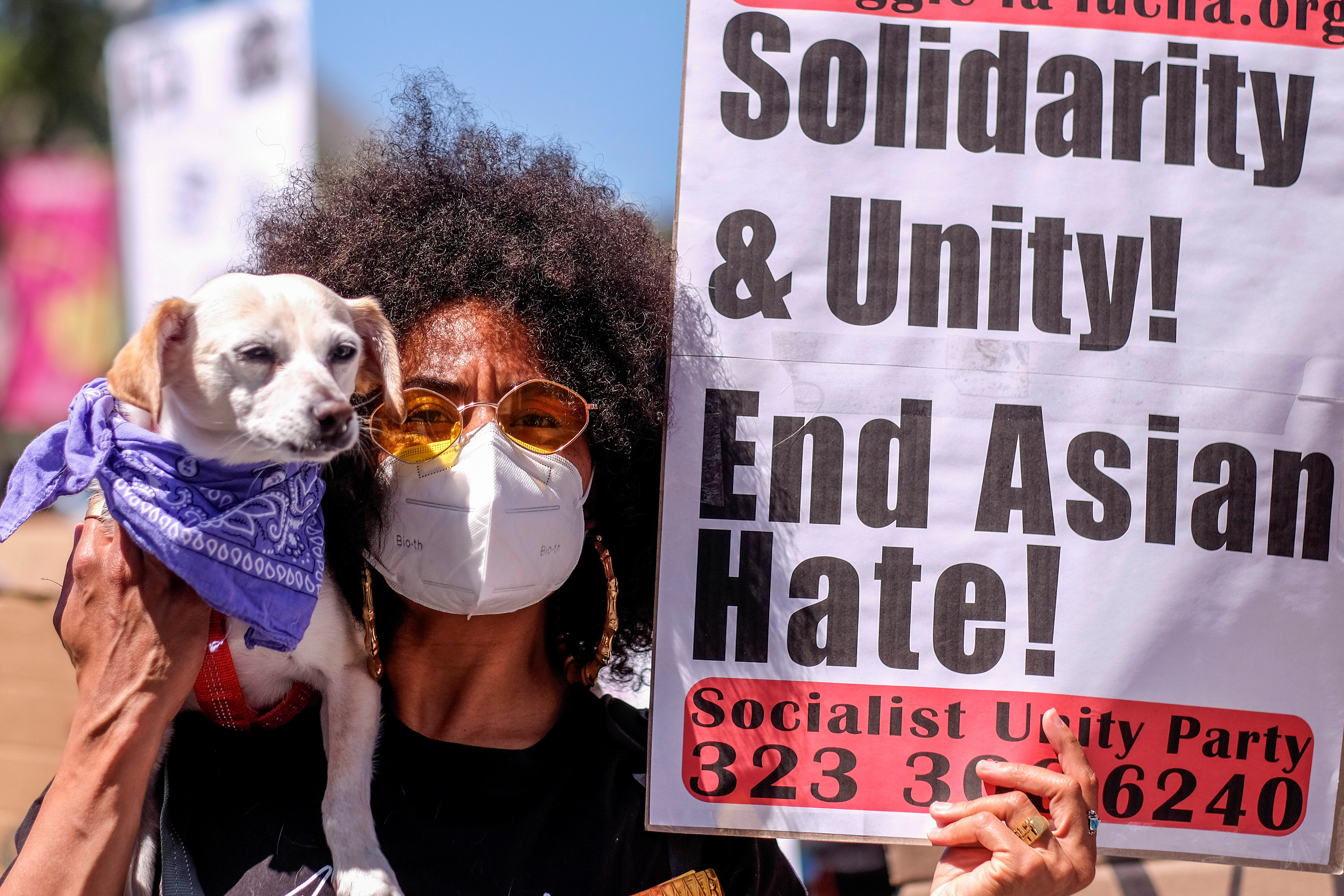 Rebecka Jackson, 35, holds her dog Sinba and a sign during a rally against anti-Asian hate crimes outside City Hall in Los Angeles, California, U.S. March 27, 2021. REUTERS/Ringo Chiu