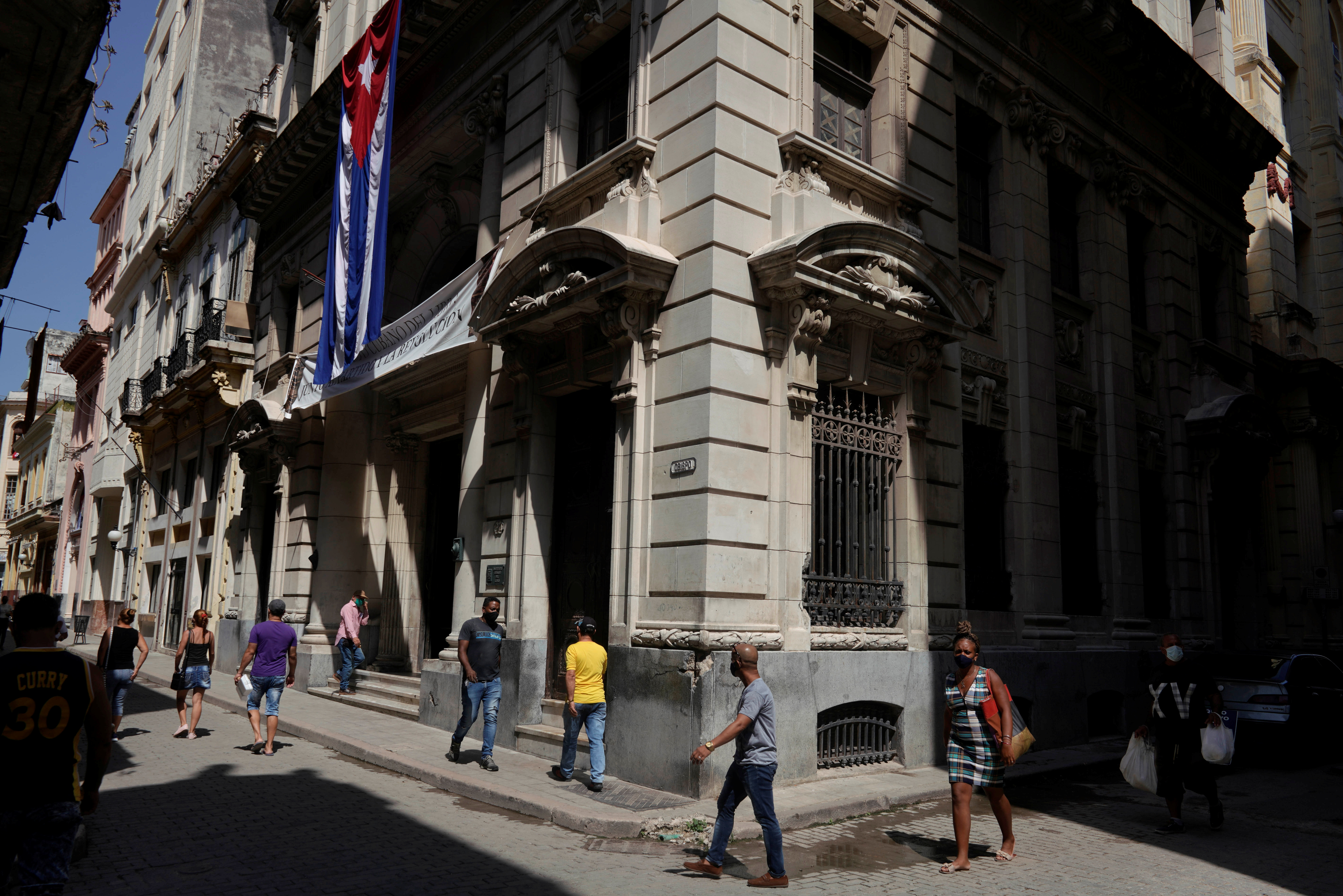 People walk under a Cuban flag at a commercial area in downtown Havana, Cuba, August 3, 2021. Photo taken on August 3, 2021. REUTERS/Alexandre Meneghini