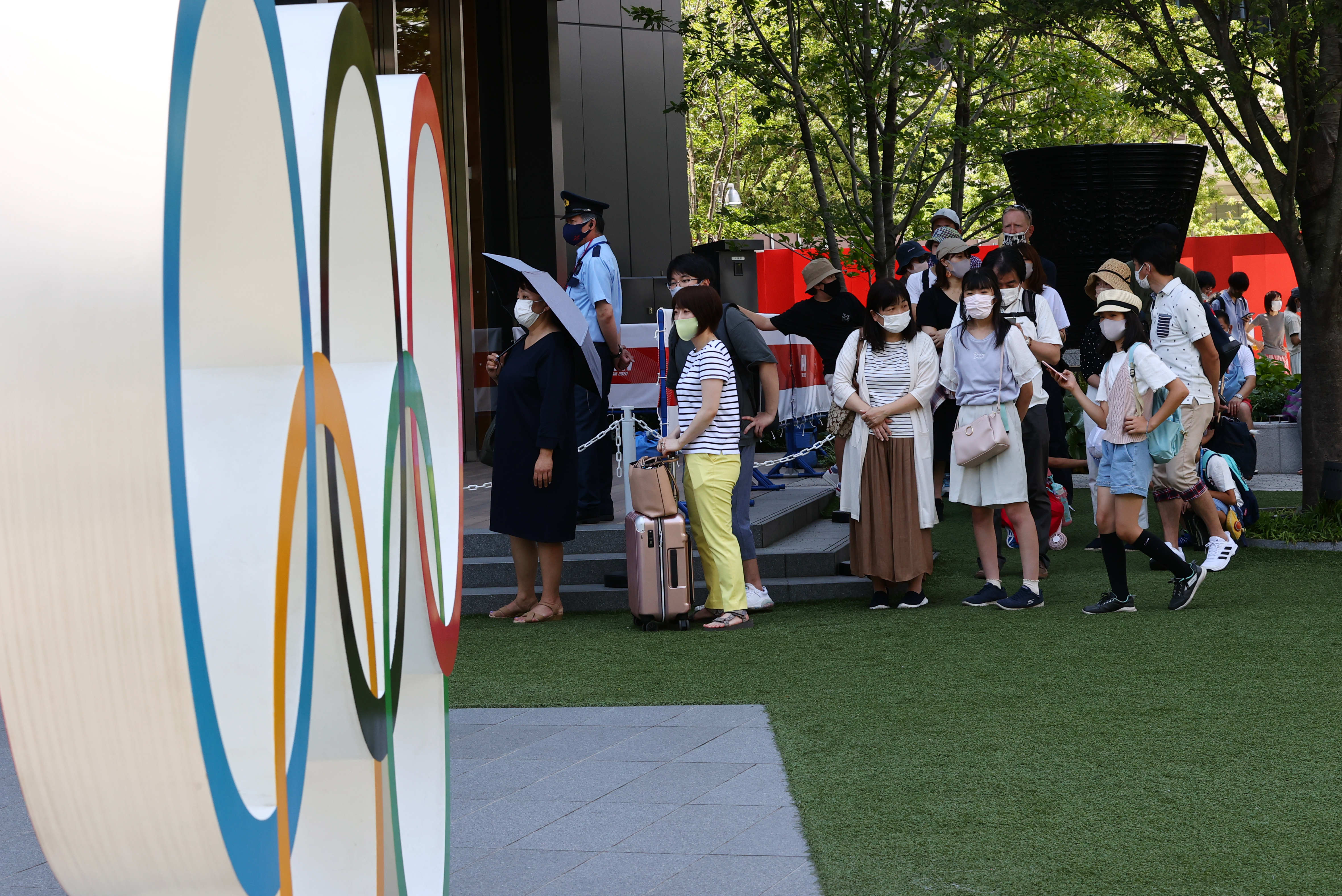 Tokyo 2020 Olympics Preview - Tokyo, Japan - July 22, 2021 People wearing protective face masks stand next to the Olympic rings REUTERS/Kim Kyung-Hoon