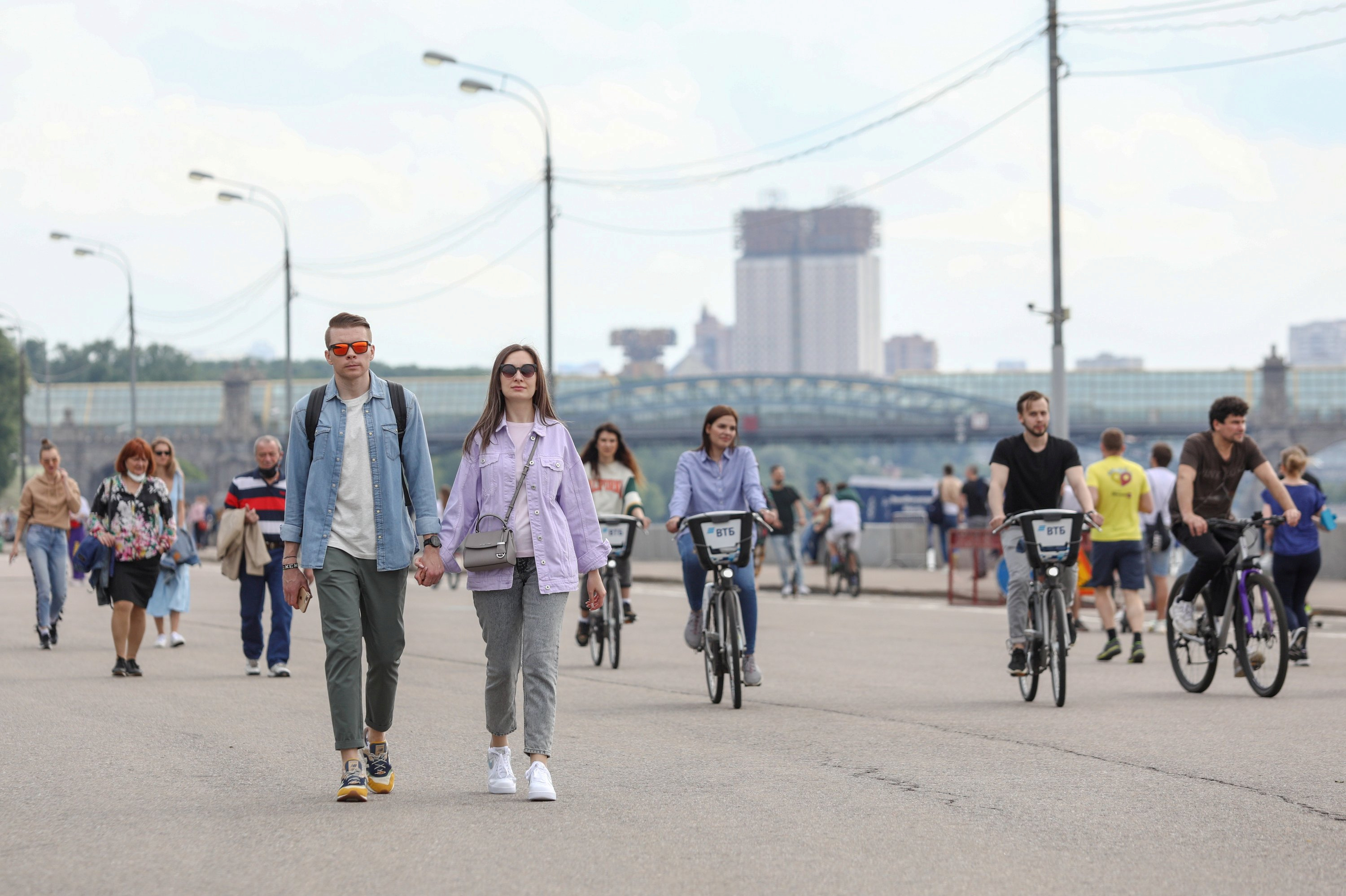People walk and ride bicycles along an embankment of the Moskva River on a warm summer day, after local authorities partially lifted quarantine restrictions imposed to prevent the spread of the coronavirus disease (COVID-19), in Moscow, Russia June 6, 2020. Kirill Zykov/Moscow News Agency/Handout via REUTERS
