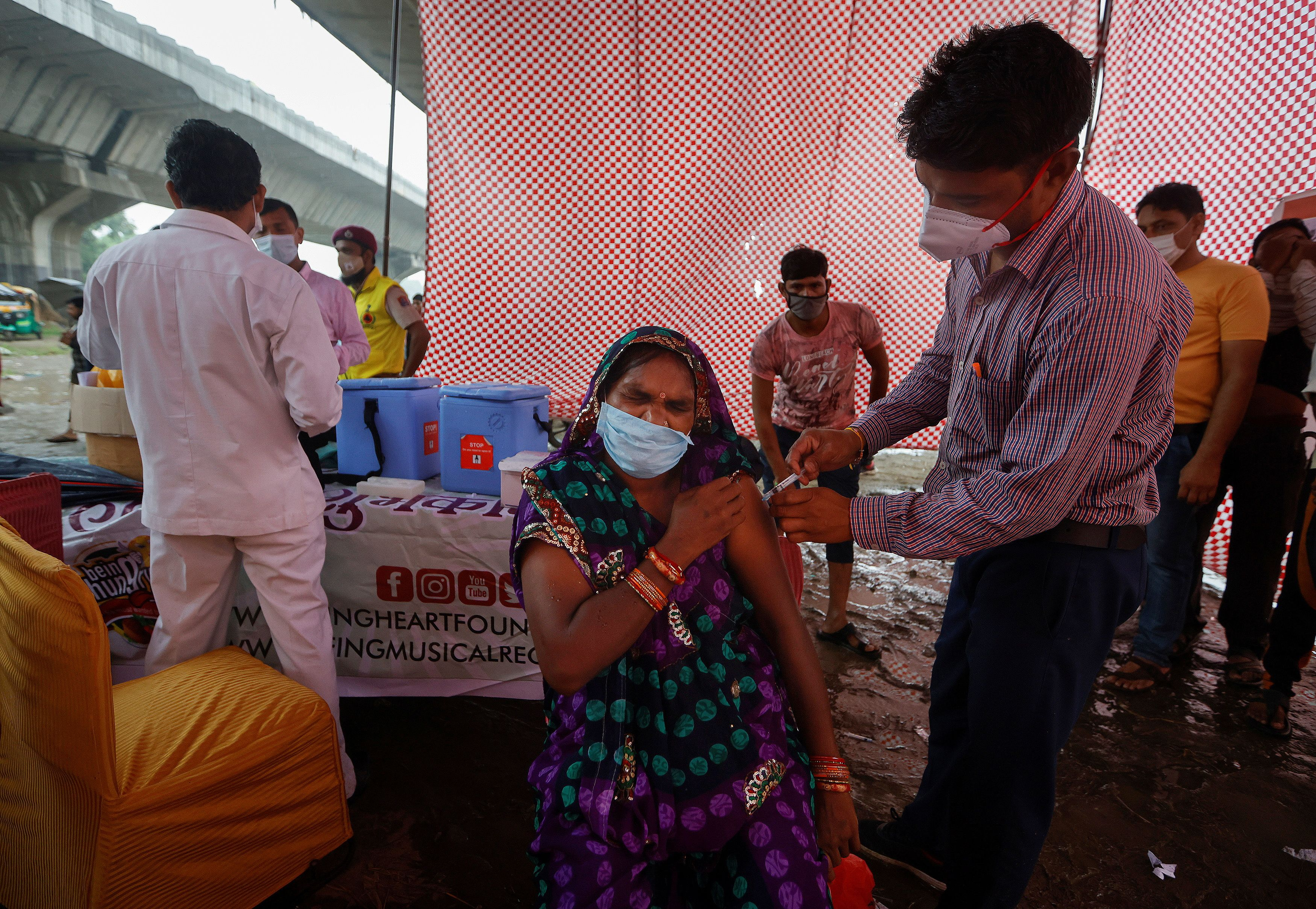 A woman receives a dose of COVAXIN coronavirus disease (COVID-19) vaccine manufactured by Bharat Biotech, during a vaccination drive organised by SEEDS, an NGO which normally specialise in providing relief after floods and other natural disasters, at an under-construction flyover in New Delhi, India, August 31, 2021. REUTERS/Adnan Abidi