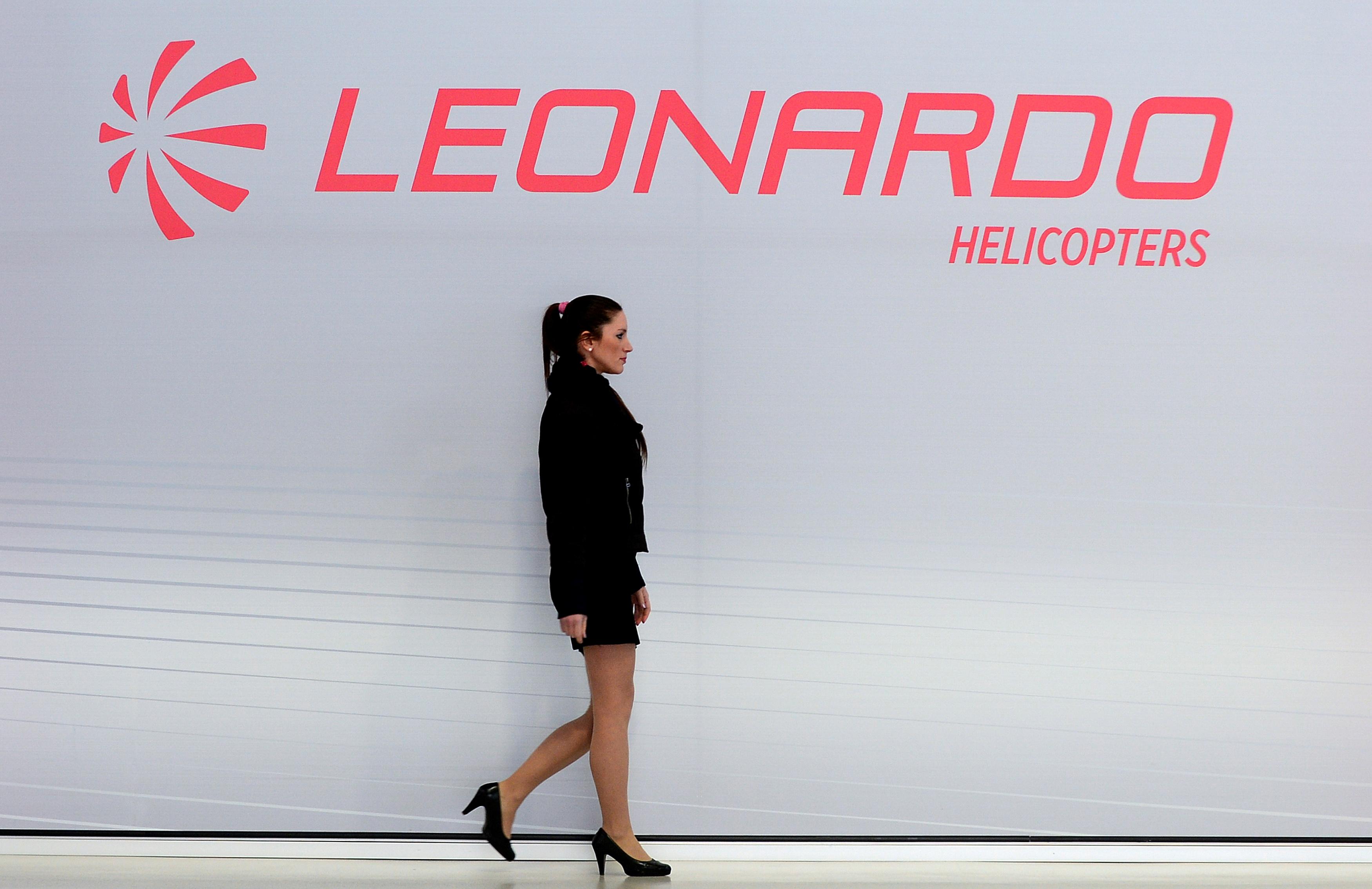 A hostess walks past a Leonardo's helicopter logo at the headquarters in Vergiate, near Milan, Italy, January 30, 2018. REUTERS/Massimo Pinca