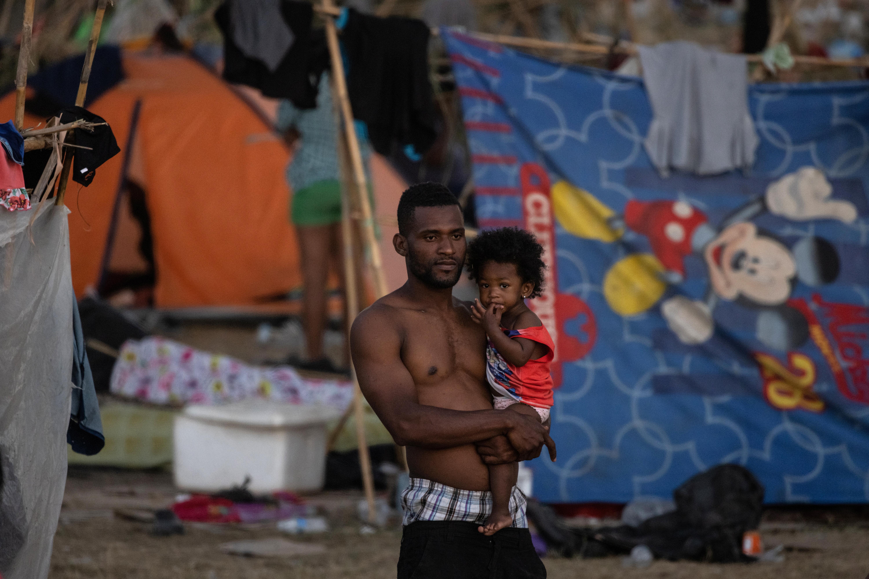 A migrant holds a girl at a makeshift border camp along the International Bridge in Del Rio, Texas, U.S. September 22, 2021. REUTERS/Adrees Latif