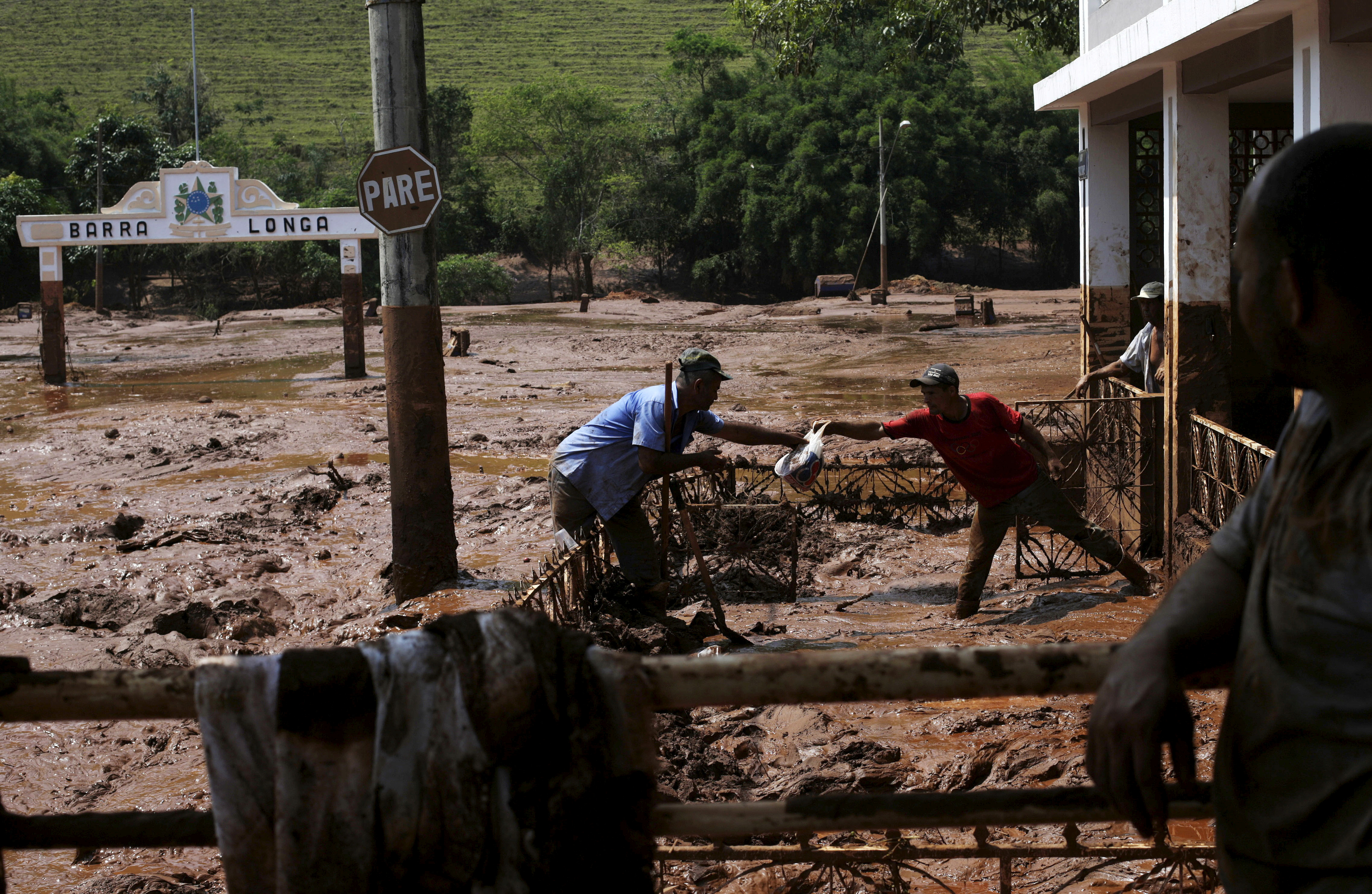 Men take out a bag from a house flooded with mud after a dam owned by Vale SA and BHP Billiton Ltd burst, in Barra Longa, Brazil, November 7, 2015. REUTERS/Ricardo Moraes/File Photo
