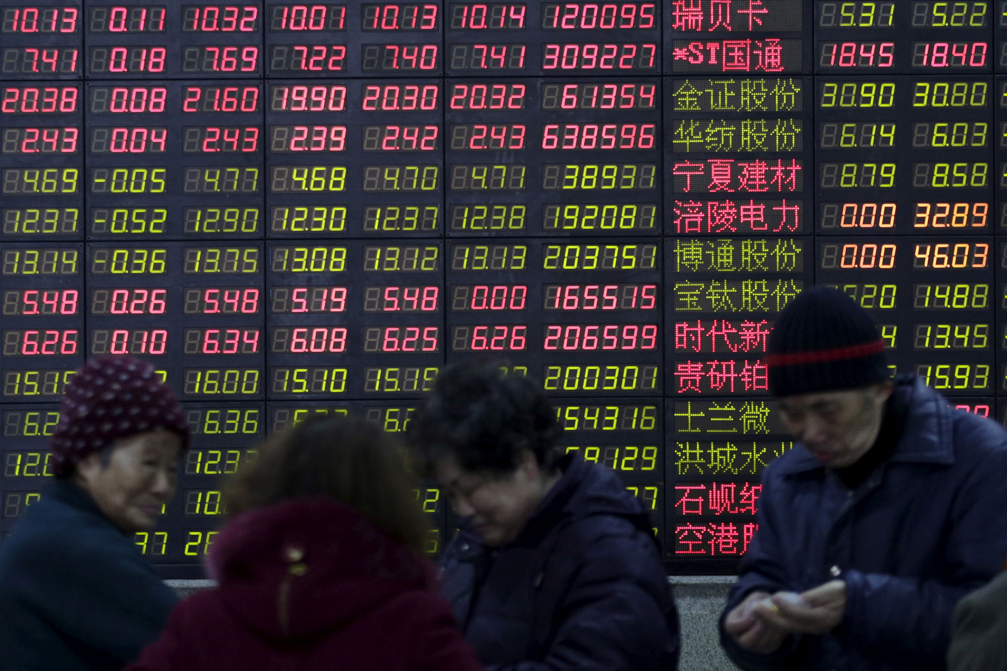 Investors stand in front of an electronic board showing stock information on the first trading day after the week-long Lunar New Year holiday at a brokerage house in Shanghai, China, February 15, 2016. REUTERS/Aly Song/File Photo
