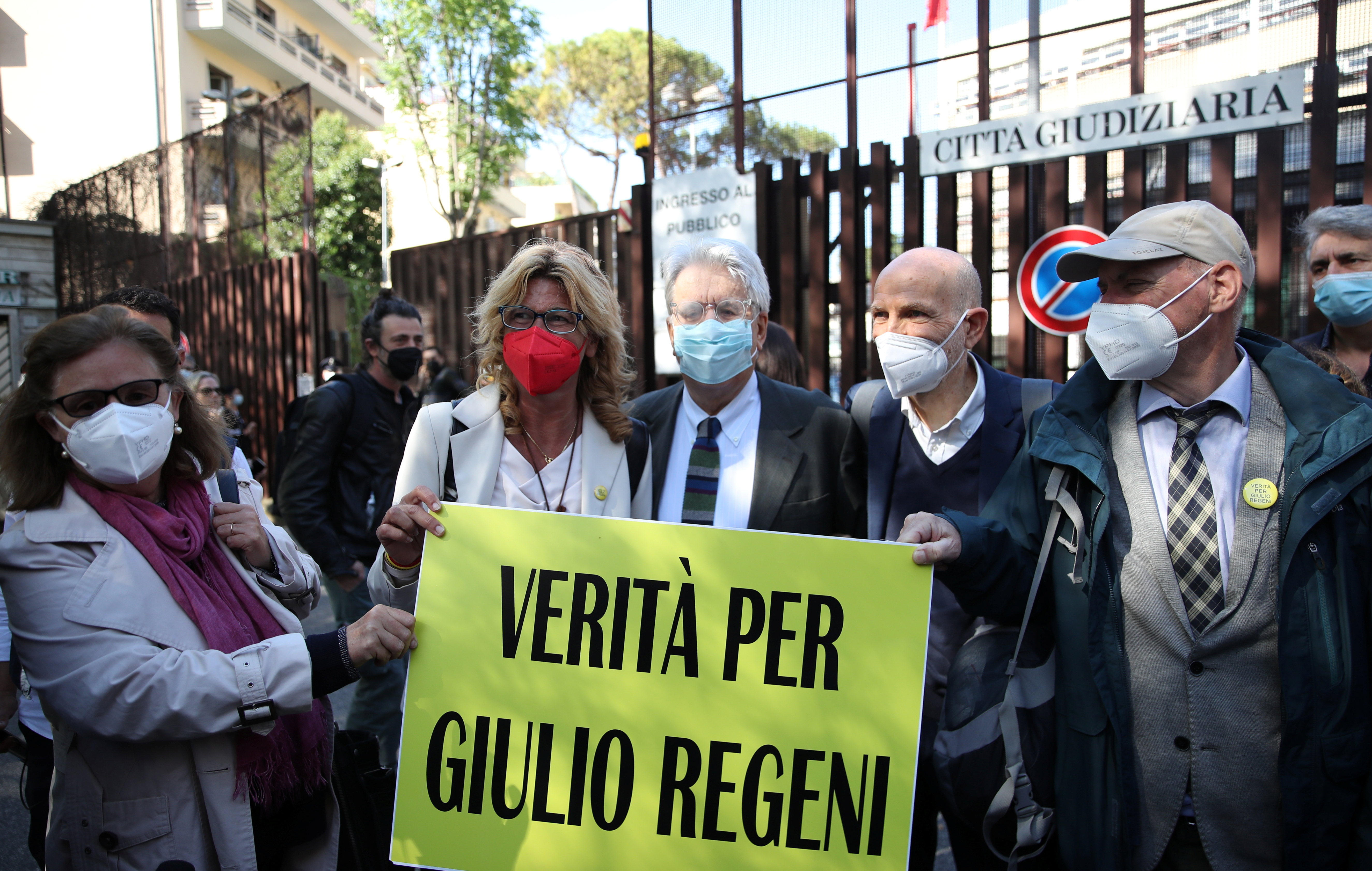 Paola and Claudio Regeni stand outside the courthouse with their lawyer Alessandra Ballerini before the pre-trial hearing to decide if four high-ranking Egyptian security officers should go on trial for the 2016 Cairo abduction, torture and killing of their son Giulio Regeni, a student, in Rome, Italy, May 25, 2021. Sign reads,