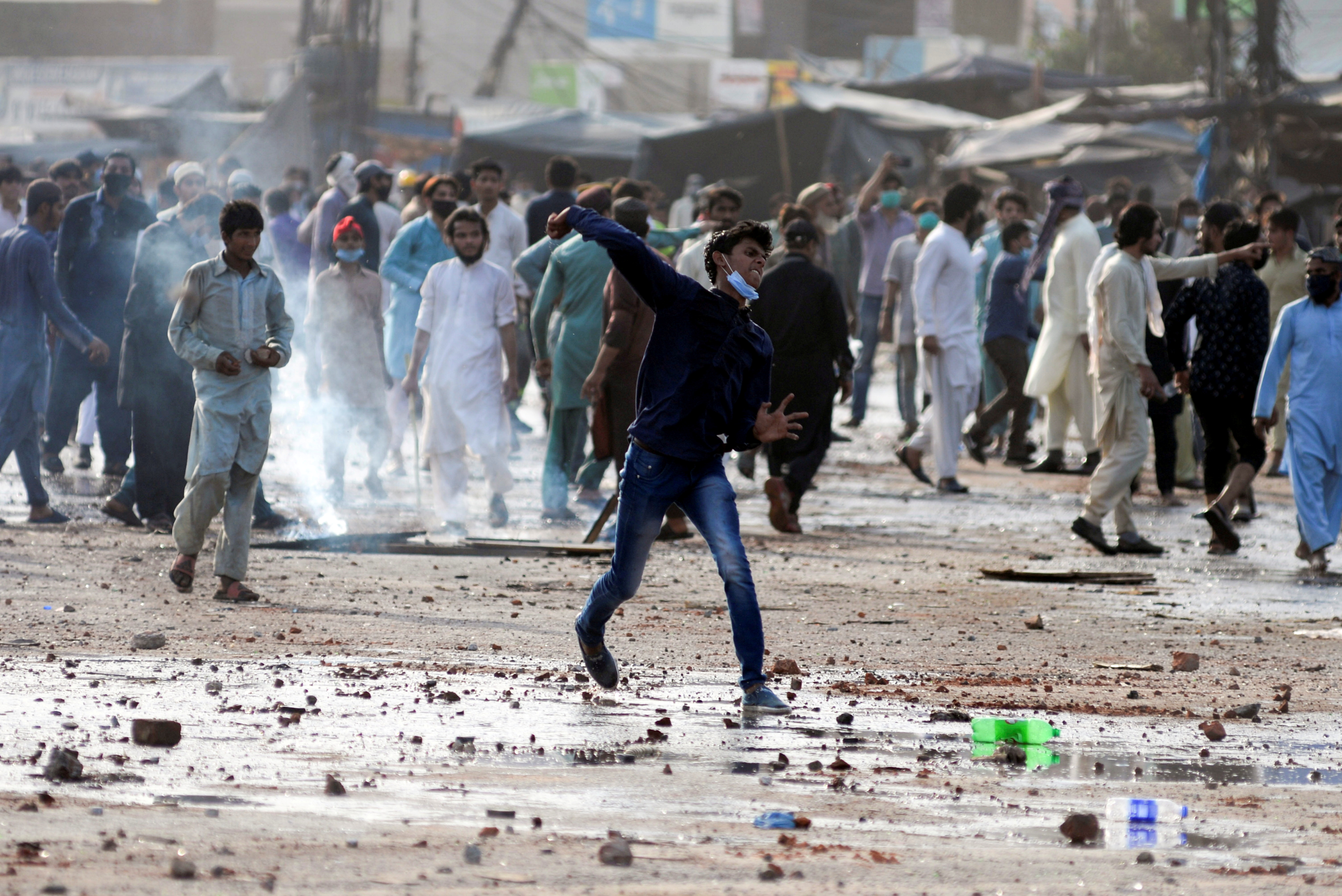 A supporter of the Tehreek-e-Labaik Pakistan (TLP) Islamist political party hurls stones towards police (not in picture) during a protest against the arrest of their leader in Lahore, Pakistan April 13, 2021. REUTERS/Stringer/File Photo