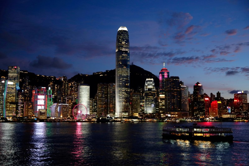 A Star Ferry boat crosses Victoria Harbour in front of a skyline of buildings during sunset. Hong Kong, China June 29, 2020. REUTERS/Tyrone Siu