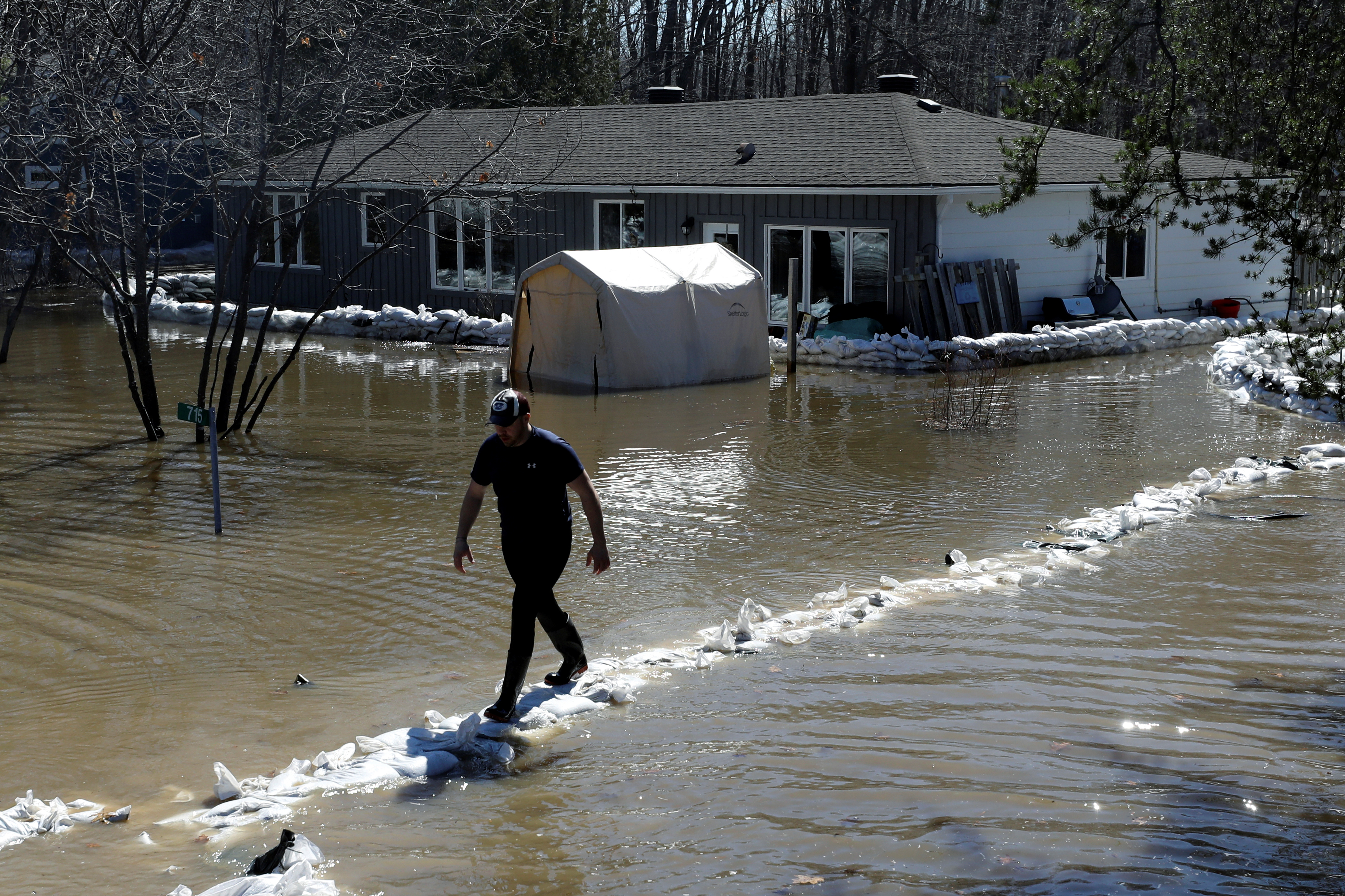 A man walks on a wall of sandbags outside a home in the flooded Constance Bay area in Ottawa, Ontario, Canada, April 30, 2019. REUTERS/Chris Wattie