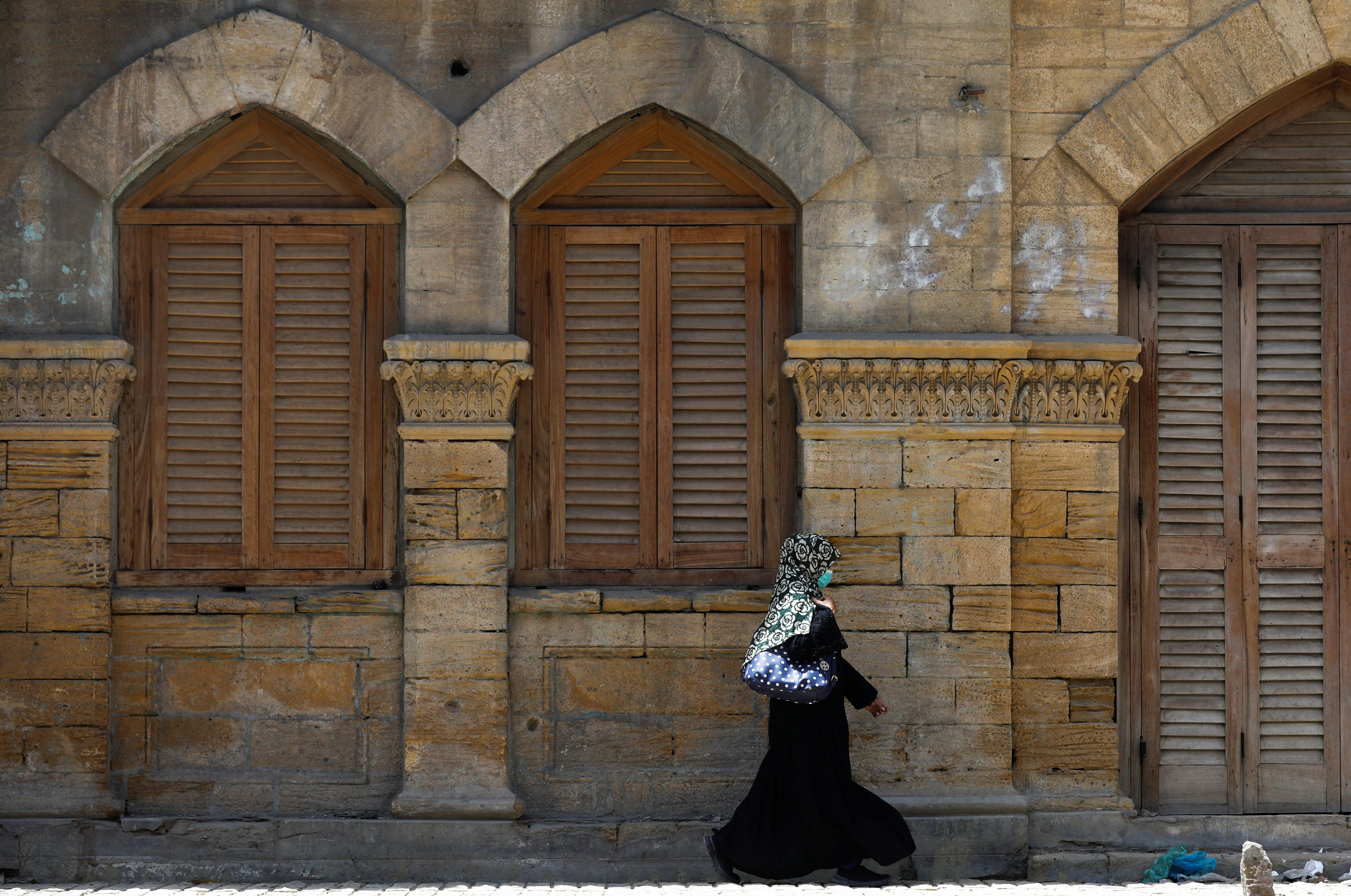 A woman wearing a protective mask walks in front of the Max Denso Hall and Library, built in memory of Max Denso during the British colonial period, as the outbreak of the coronavirus disease (COVID-19) continues, in Karachi, Pakistan April 23, 2021. REUTERS/Akhtar Soomro
