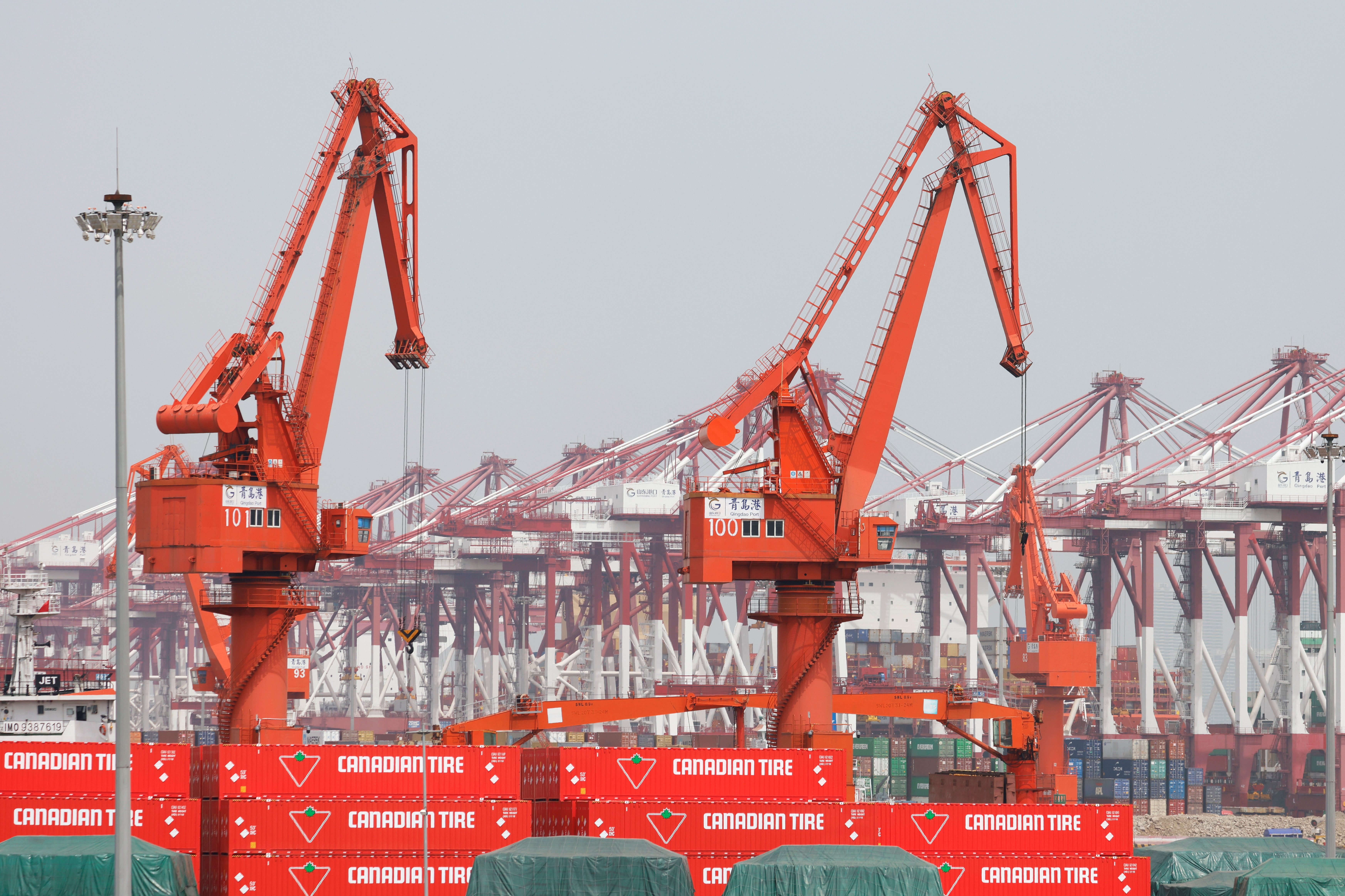 Canadian Tire containers are seen near cranes at Qingdao port in Shandong province, China, following an oil spill in the Yellow Sea caused by a collision between tanker A Symphony and bulk vessel Sea Justice off the port, April 28, 2021. REUTERS/Carlos Garcia Rawlins