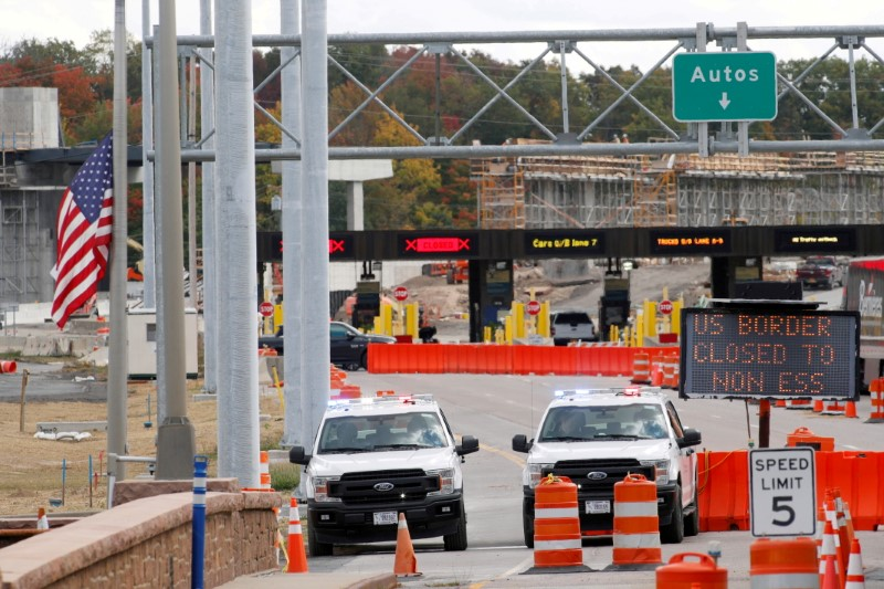 U.S. customs vehicles stand near a sign reading that the border is closed to non-essential traffic, at the Canada-United States border crossing at the Thousand Islands Bridge, to combat the spread of the coronavirus disease (COVID-19) in Lansdowne, Ontario, Canada September 28, 2020.  REUTERS/Lars Hagberg/File Photo