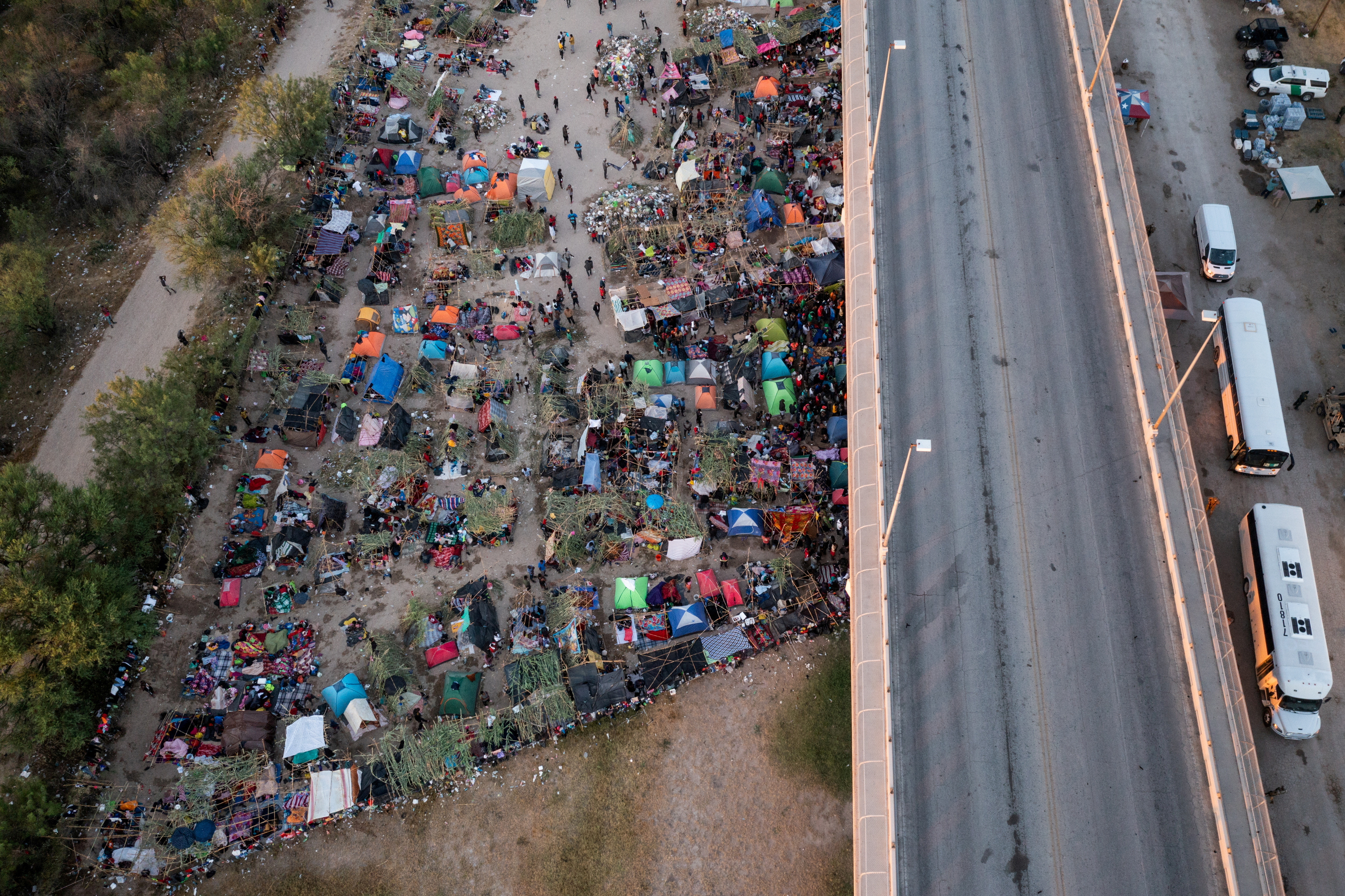 Vehicles await to transport migrants as they shelter along the Del Rio International Bridge after crossing the Rio Grande river into the U.S. from Ciudad Acuna in Del Rio, Texas, U.S. September 19, 2021. Picture taken with a drone. REUTERS/Adrees Latif/File Photo