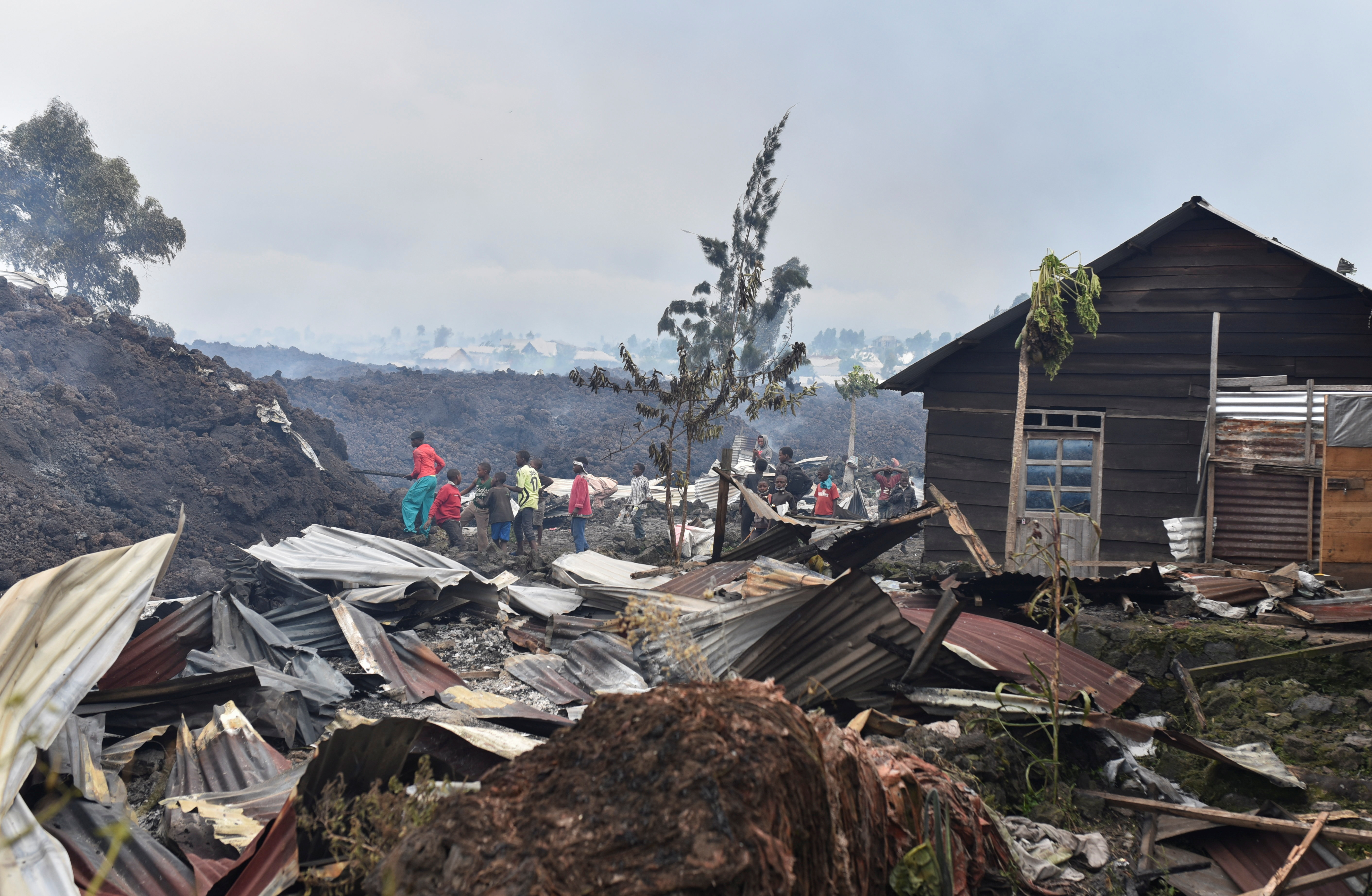 Residents pick up remains of their destroyed homes from the smouldering lava deposited by the eruption of Mount Nyiragongo volcano near Goma, in the Democratic Republic of Congo May 23, 2021. REUTERS/Olivia Acland
