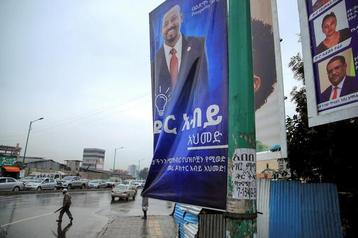 A man walks past an election campaign billboard depicting Ethiopian Prime Minister Abiy Ahmed, in Addis Ababa, Ethiopia, June 14, 2021. REUTERS/Tiksa Negeri/File Photo