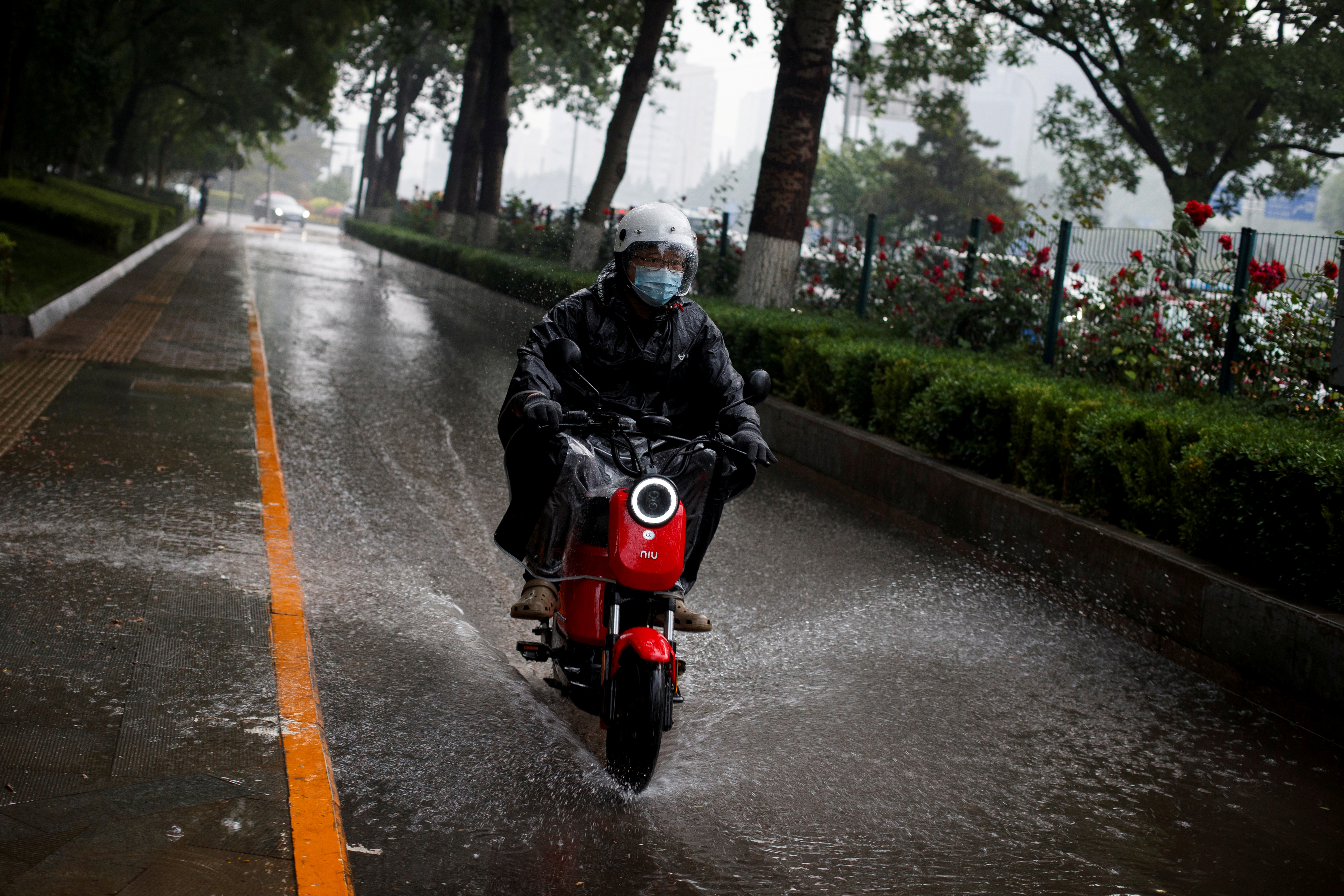 A man rides a Niu electric scooter through a puddle in Beijing, China May 21, 2020. REUTERS/Thomas Peter/File Photo