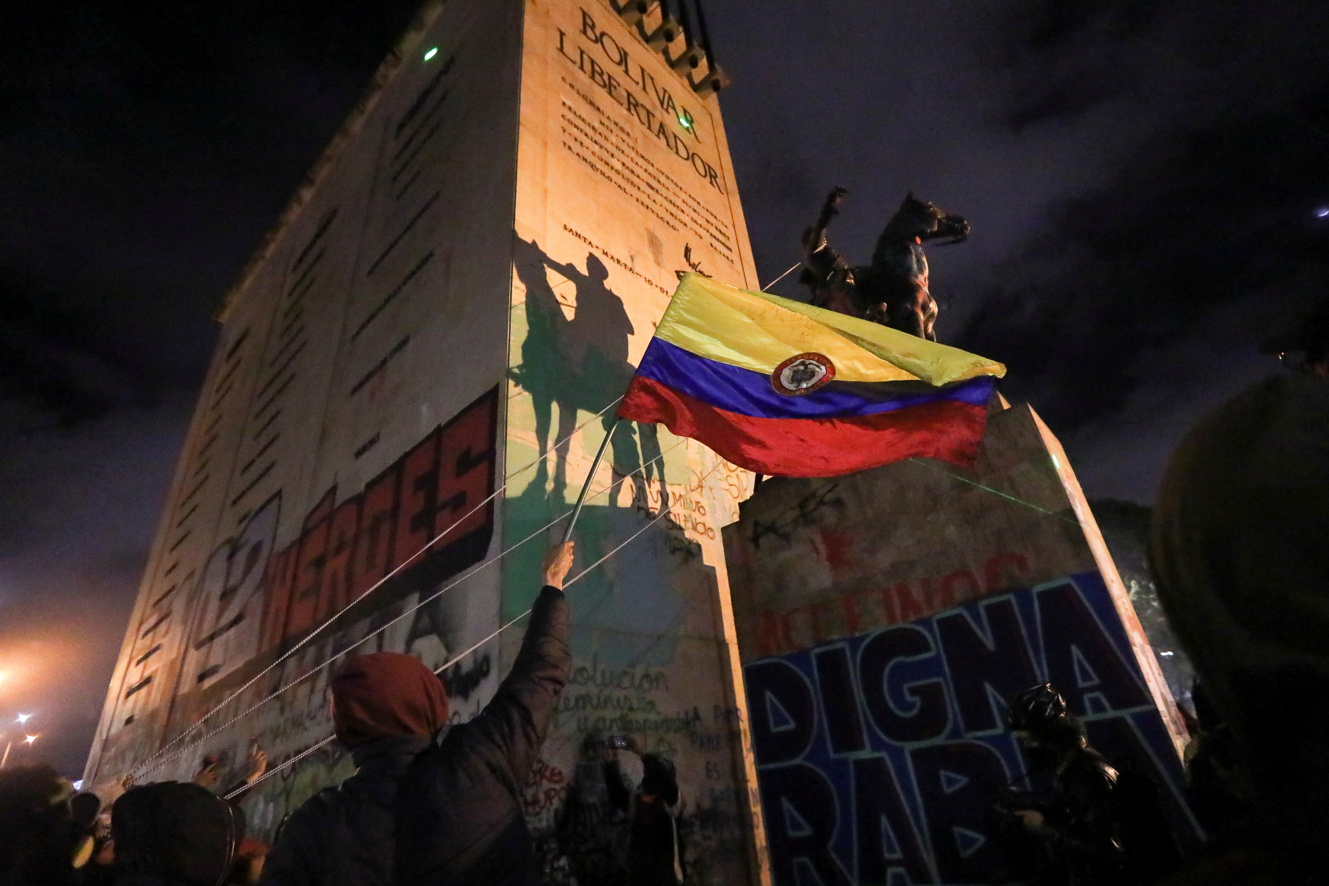 People try to topple the statue of South American independence leader Simon Bolivar during a protest against sexual assault by the police and the excess of public force against peaceful protests, in Bogota, Colombia, May 15, 2021. REUTERS/Luisa Gonzalez