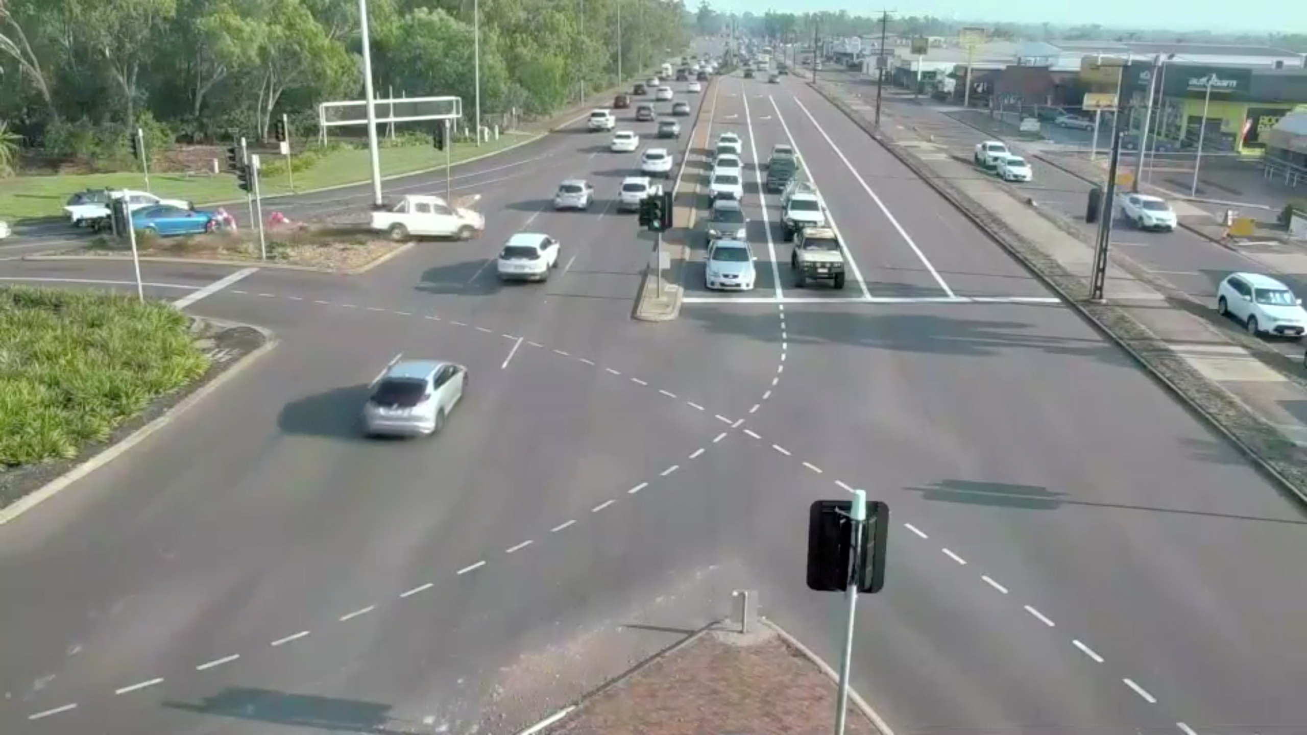 A white Toyota Hilux (L, near post) is seen speeding down horizontally across lanes of traffic in Darwin, Australia, September 23, 2021, in this still image taken from video obtained from social media. According to police, the passengers in the car were conveyed to a hospital with non-life -threatening injuries. Video taken September 23, 2021. Mandatory credit NORTHERN TERRITORY POLICE, FIRE AND EMERGENCY SERVICES/via REUTERS