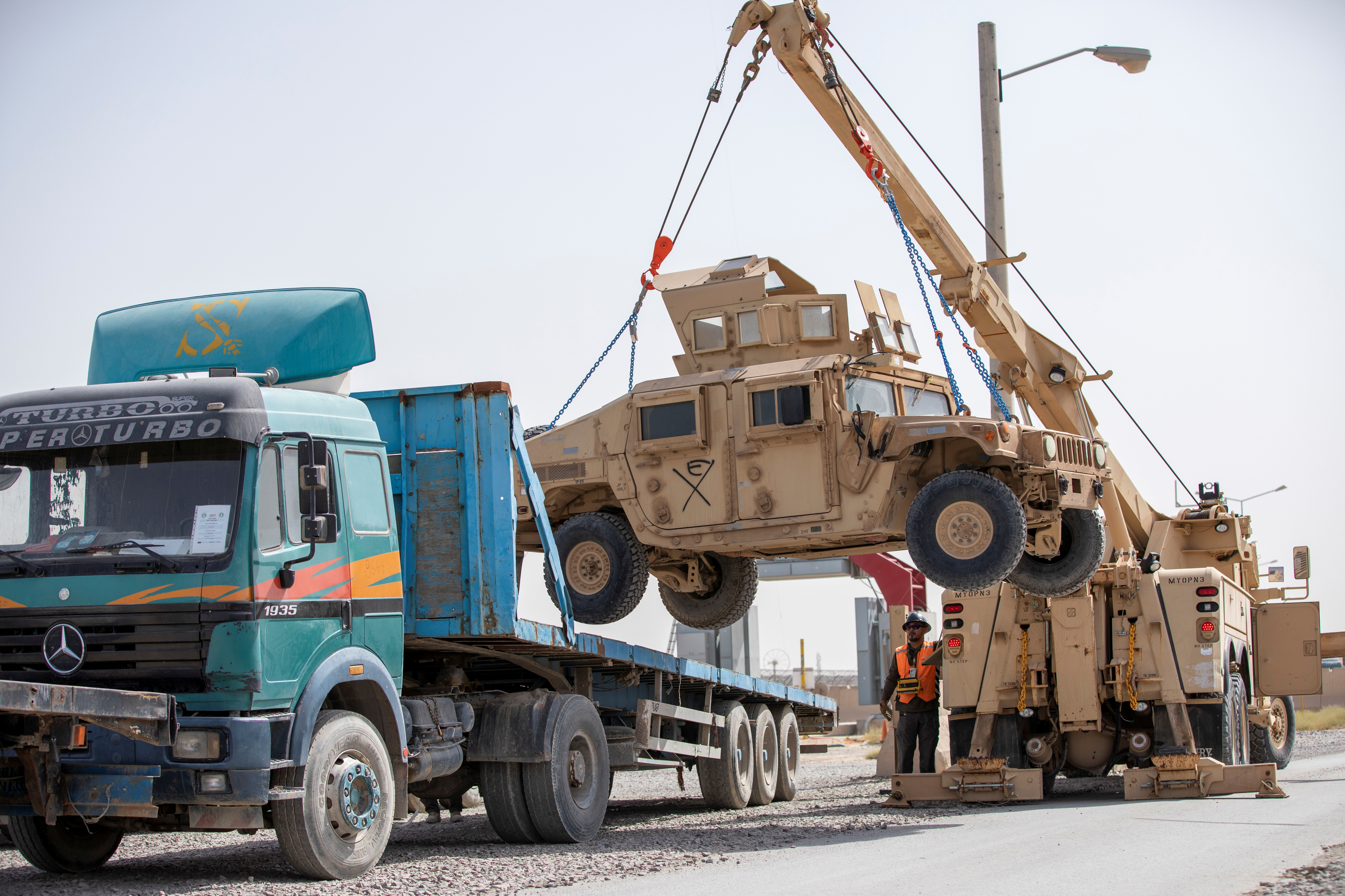 U.S. Army soldiers and contractors load High Mobility Multi-purposed Wheeled Vehicles, HUMVs, to be sent for transport as U.S. forces prepare for withdrawl, in Kandahar, Afghanistan, July 13, 2020. Picture taken July 13, 2020. U.S. Army/Sgt. Jeffery J. Harris/Handout via REUTERS THIS IMAGE HAS BEEN SUPPLIED BY A THIRD PARTY.