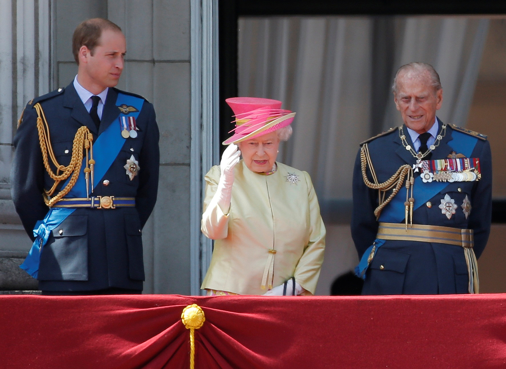 Britain's Queen Elizabeth waves as she stands with Prince William (L) and Prince Philip as they prepare to view a RAF flypast to mark the 75th anniversary of the Battle of Britain, from the balcony of Buckingham Palace in London, Britain July 10, 2015. REUTERS/Peter Nicholls/File Photo