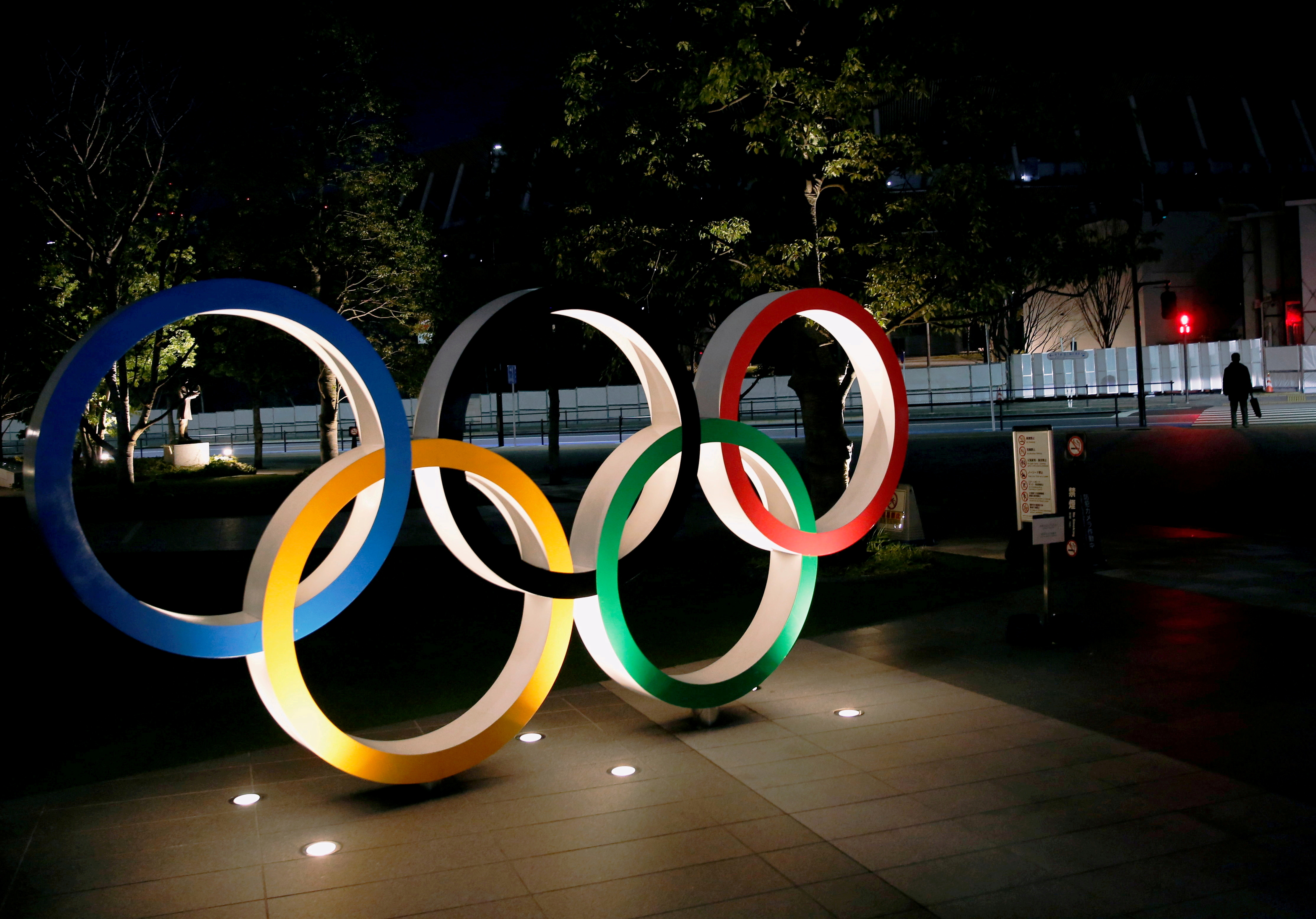 The Olympic rings are illuminated in front of the National Stadium in Tokyo, Japan January 22, 2021. REUTERS/Kim Kyung-Hoon/File Photo