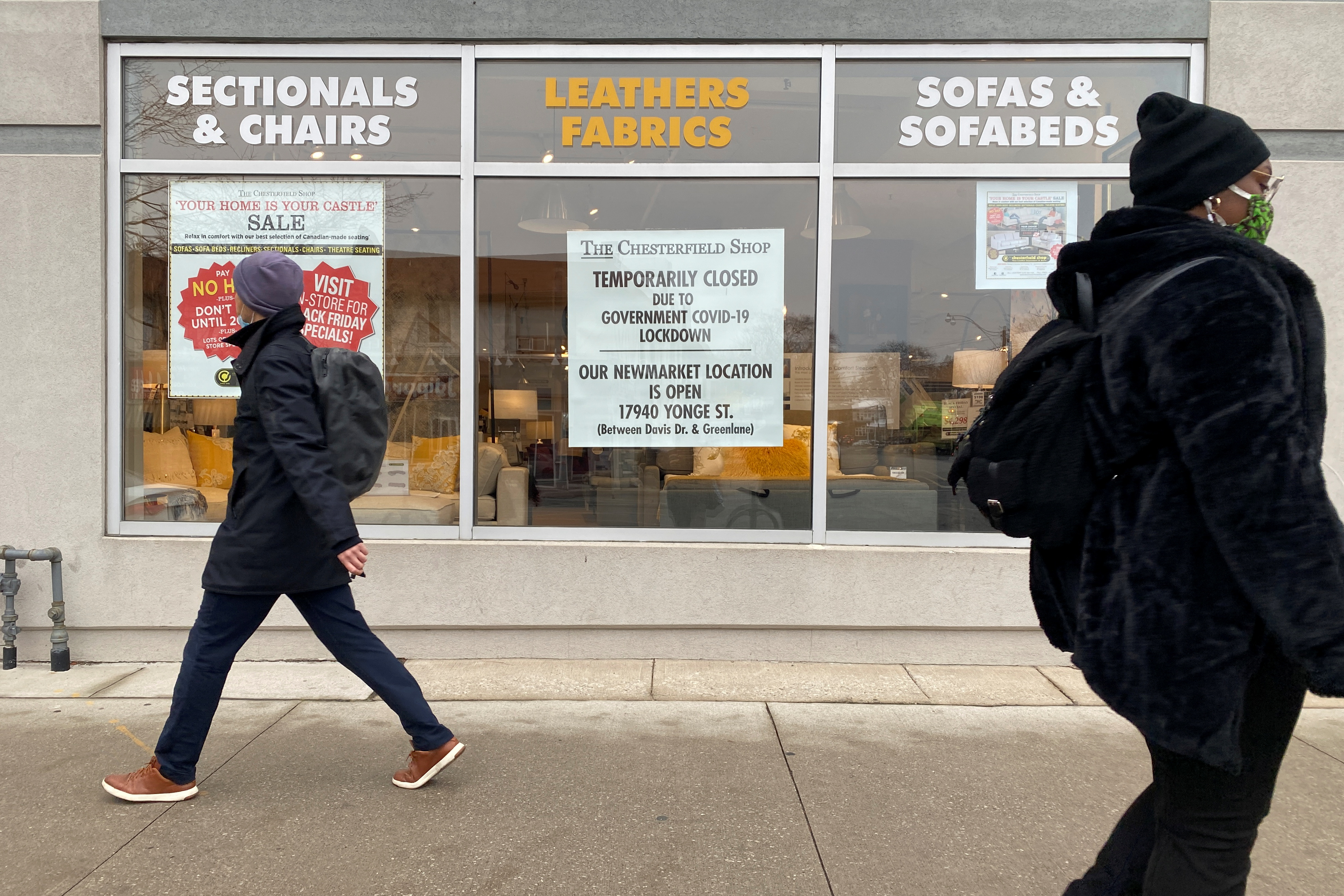 People pass by a furniture store which was closed as part of the reintroduction of anti-coronavirus disease (COVID-19) restrictions in Toronto, Ontario, Canada November 25, 2020. REUTERS/Chris Helgren