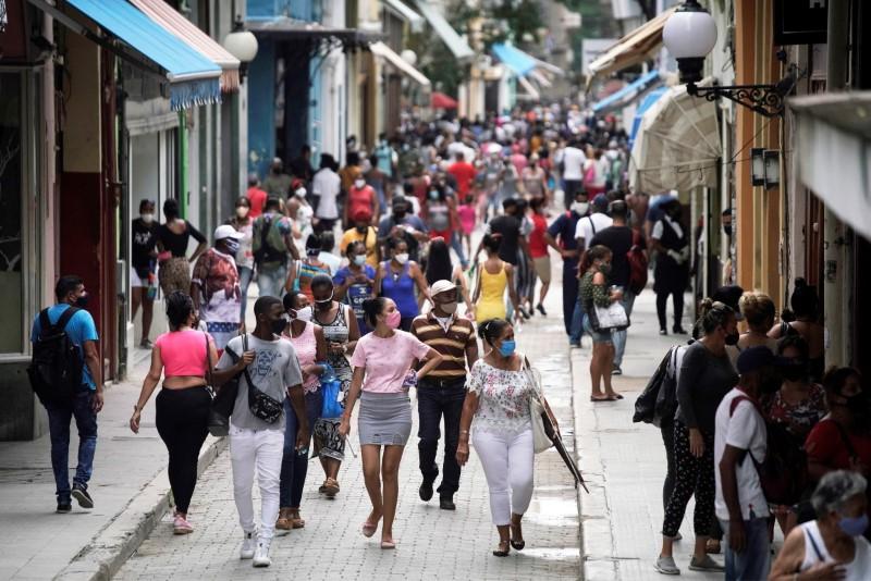 People walk in a commercial street in Havana, Cuba, June 15, 2021. Picture taken on June 15, 2021. REUTERS/Alexandre Meneghini