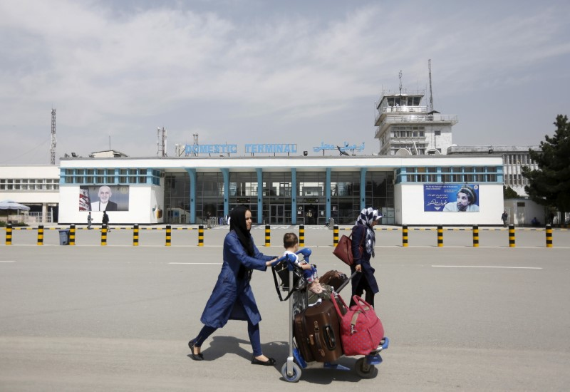 Afghan passengers walk in front of Hamid Karzai International Airport in Kabul, Afghanistan March 29, 2016.  REUTERS/Omar Sobhani/File Photo