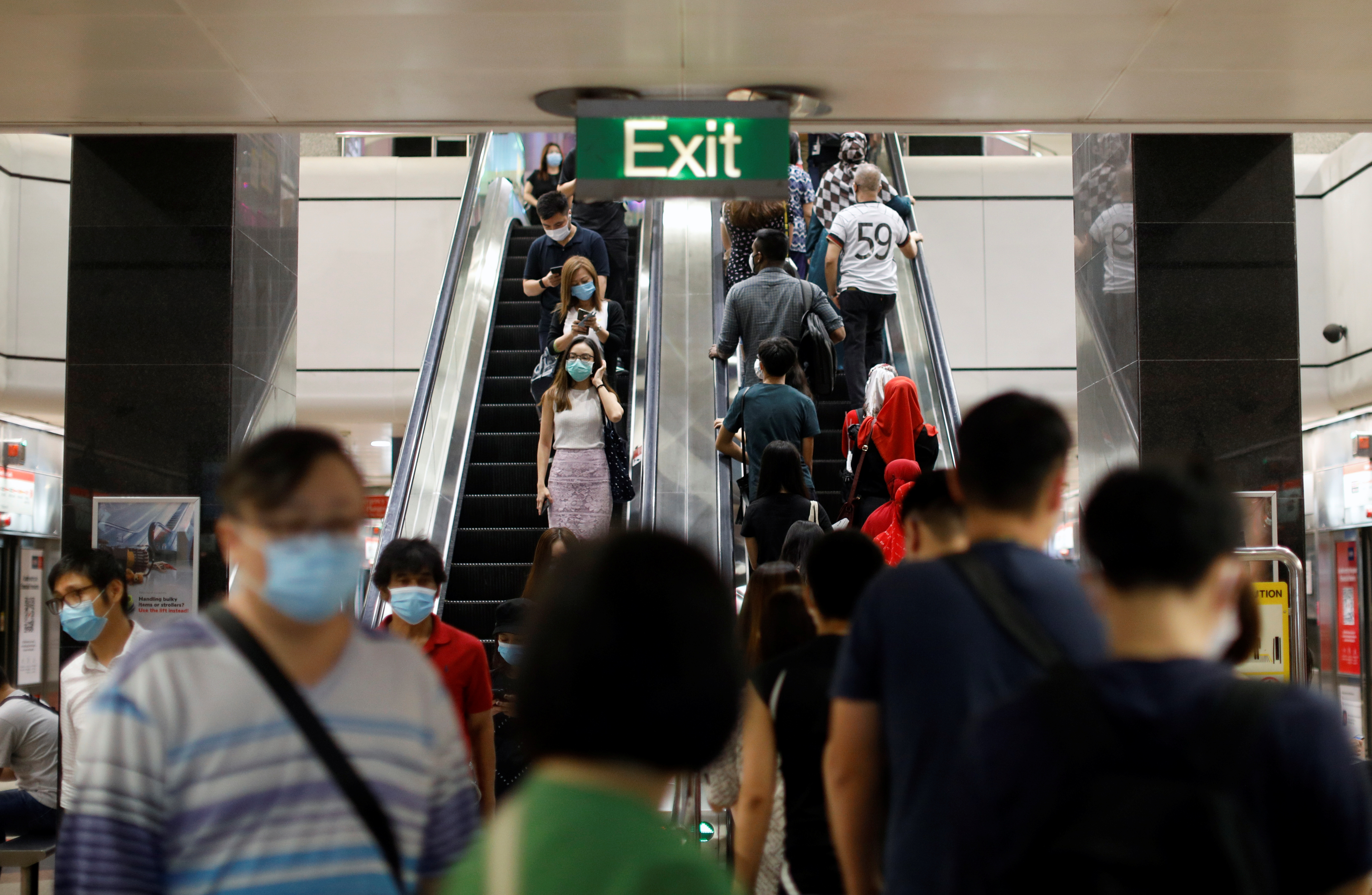 Commuters wearing protective face masks leave a train station during the coronavirus disease (COVID-19) outbreak in Singapore August 17, 2020.   REUTERS/Edgar Su